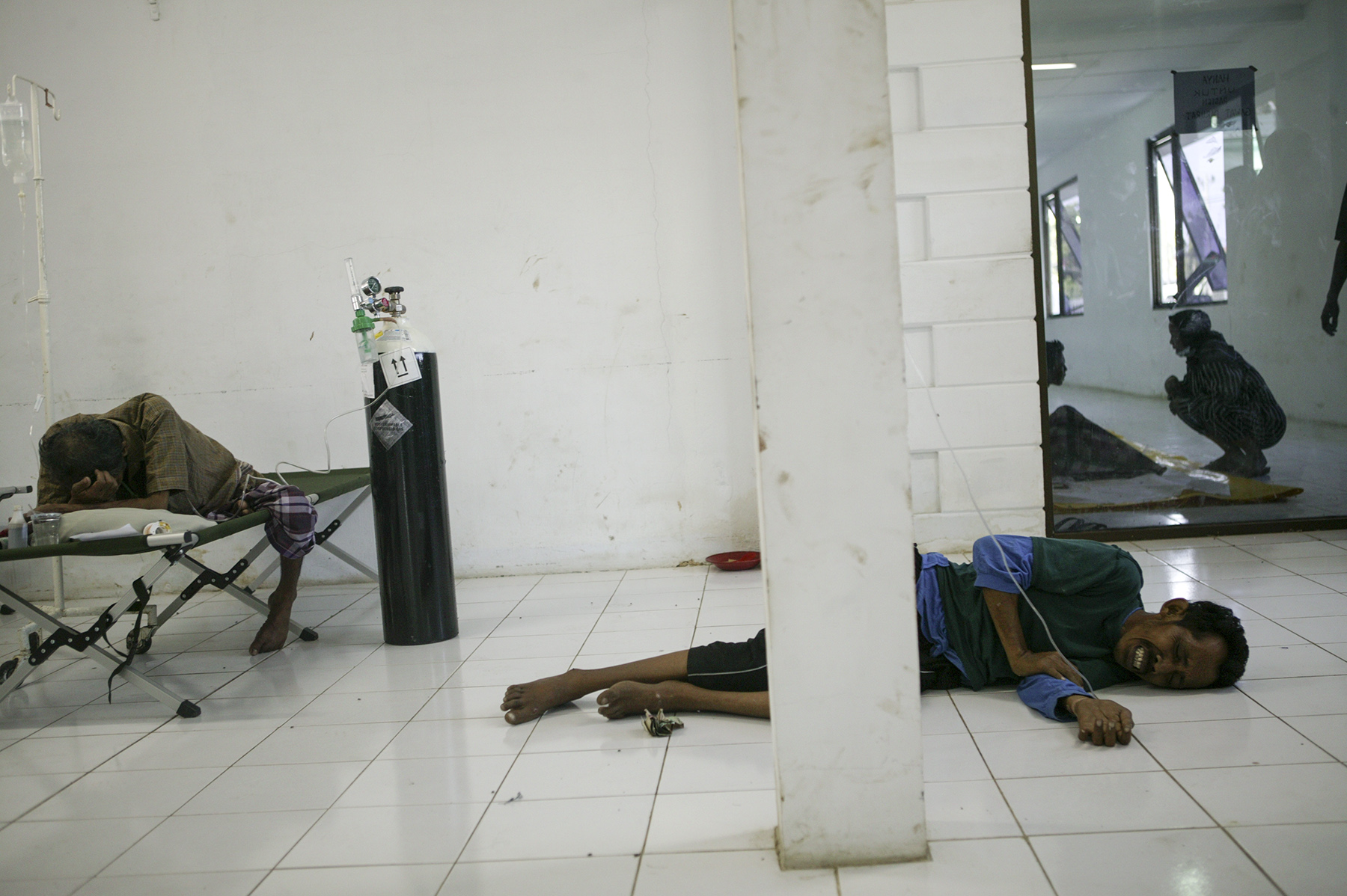Injured survivors wait for medical attention at the emergency room of a hospital in Banda Aceh.