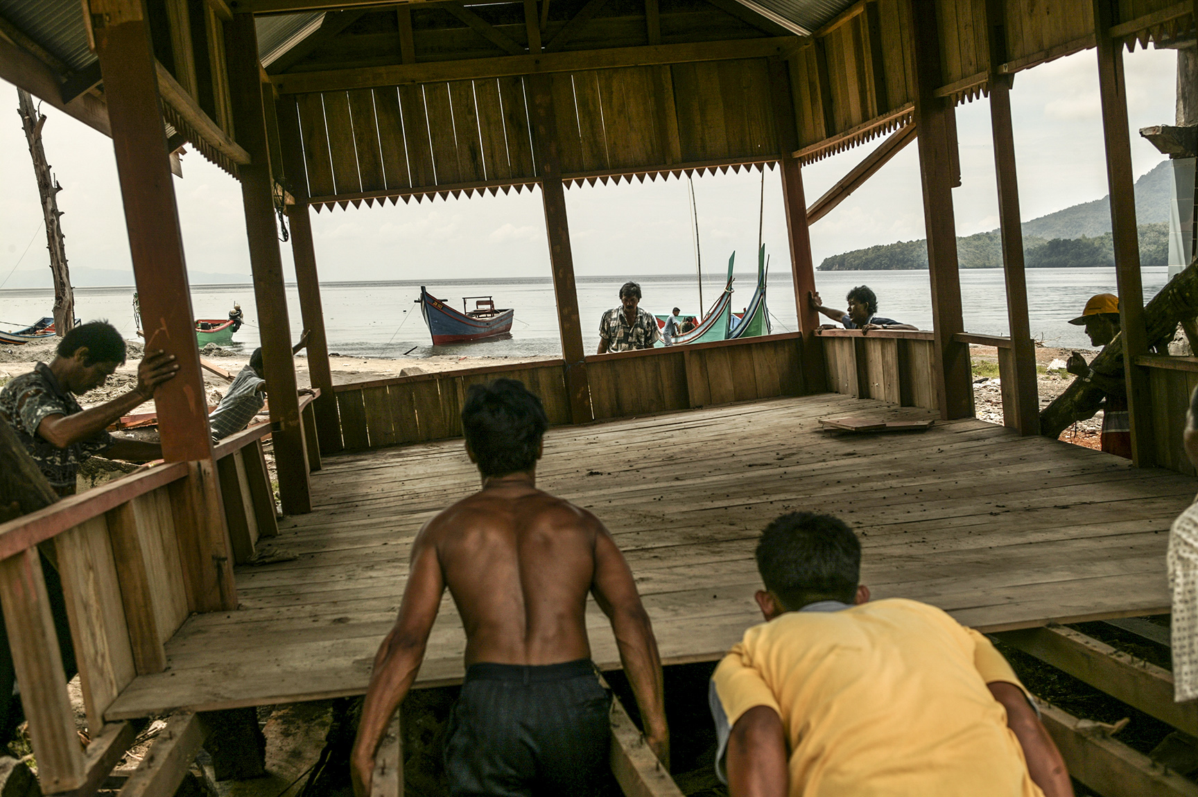 Locals of a fishing community work together to rebuild their homes.