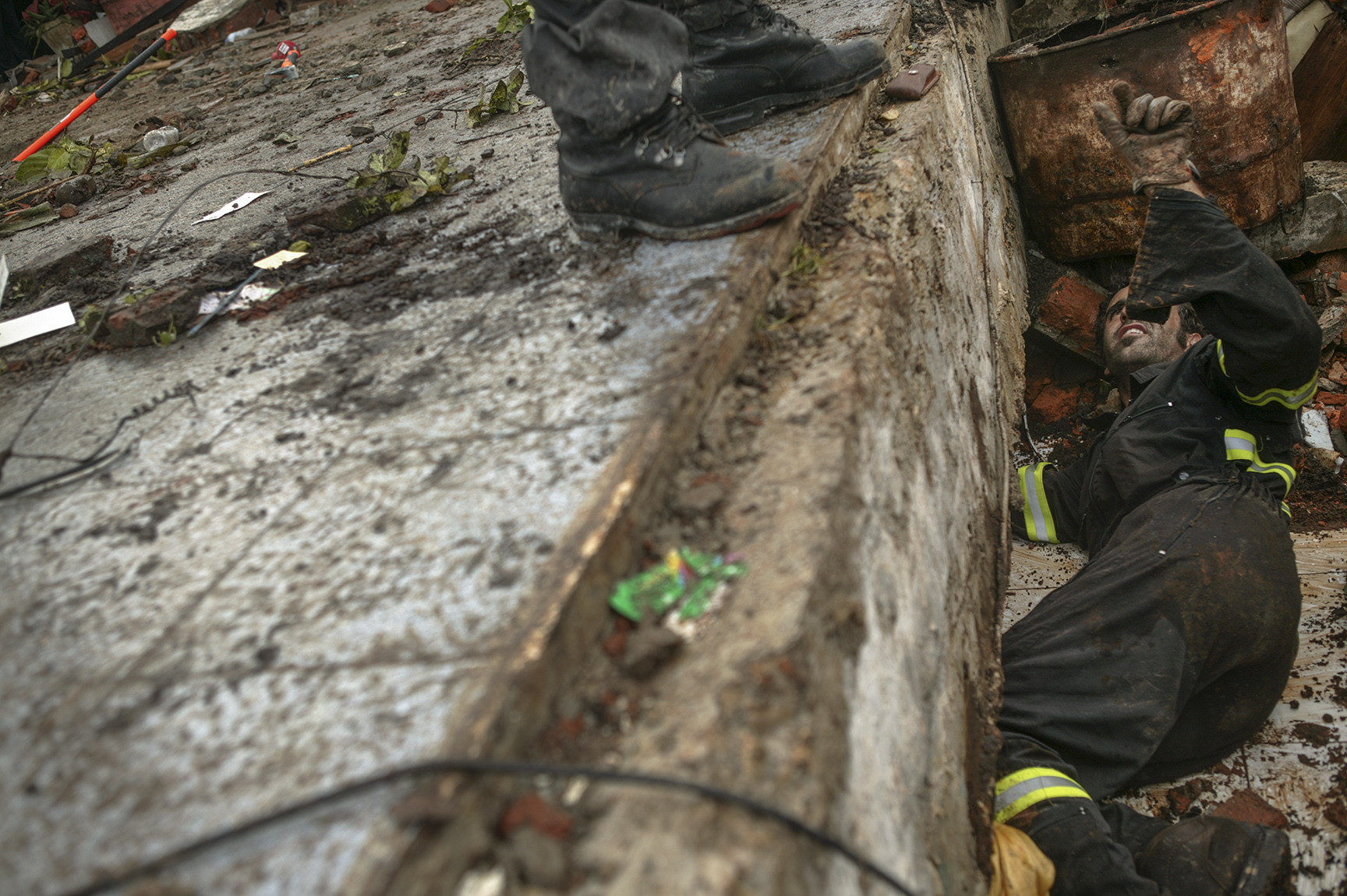 A Spanish search and rescue team searches a collapsed building for survivors.