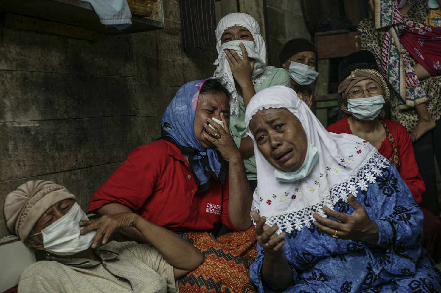 A family grieves as a deceased family member is extracted from the collapsed section of their home.