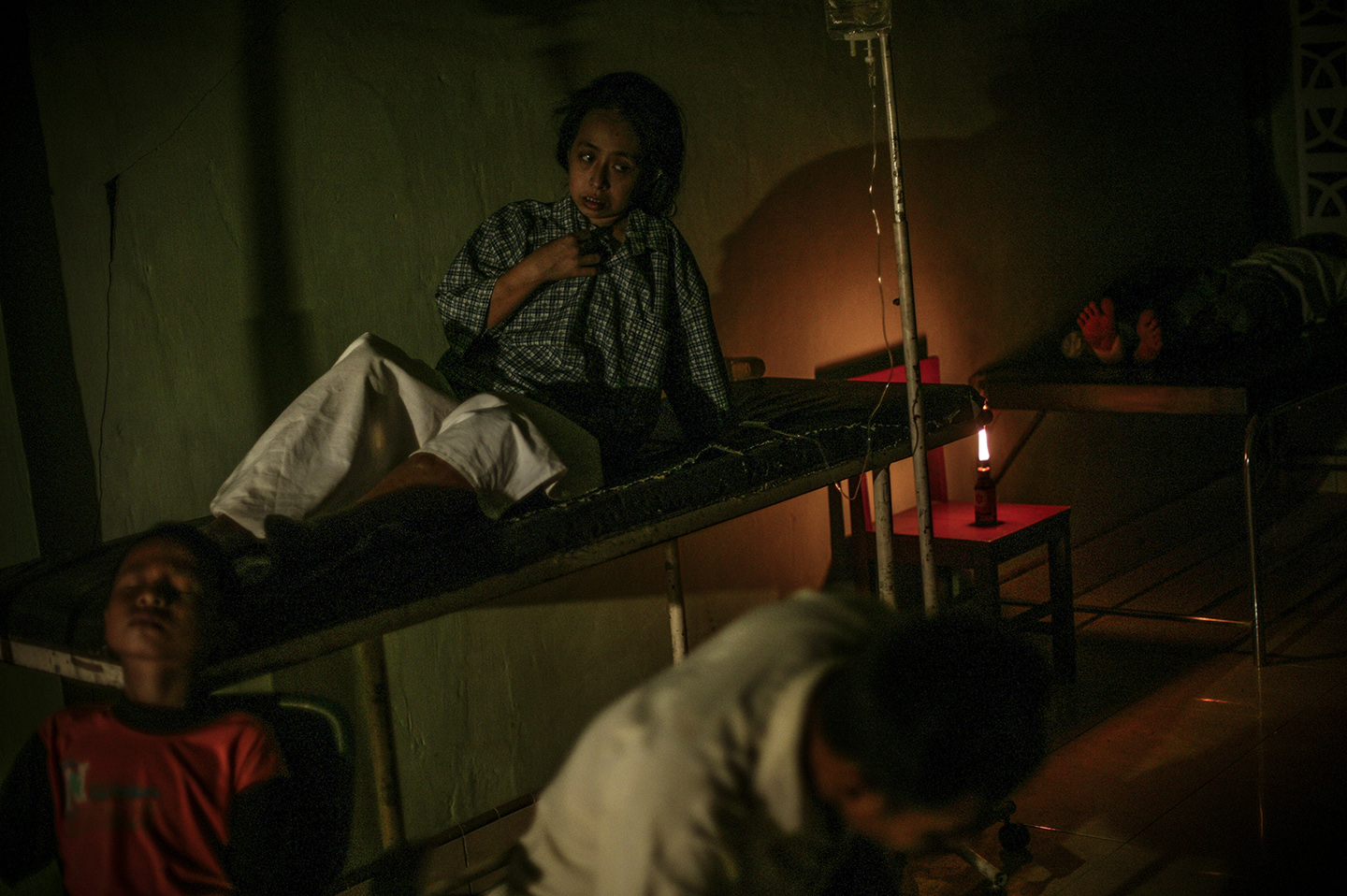 Injured survivors by candlelight at the city's local hospital. The hospital ran without electricity for the first three days after the earthquake. Most of the hospital rooms were destroyed so patients were treated in the lobby area.