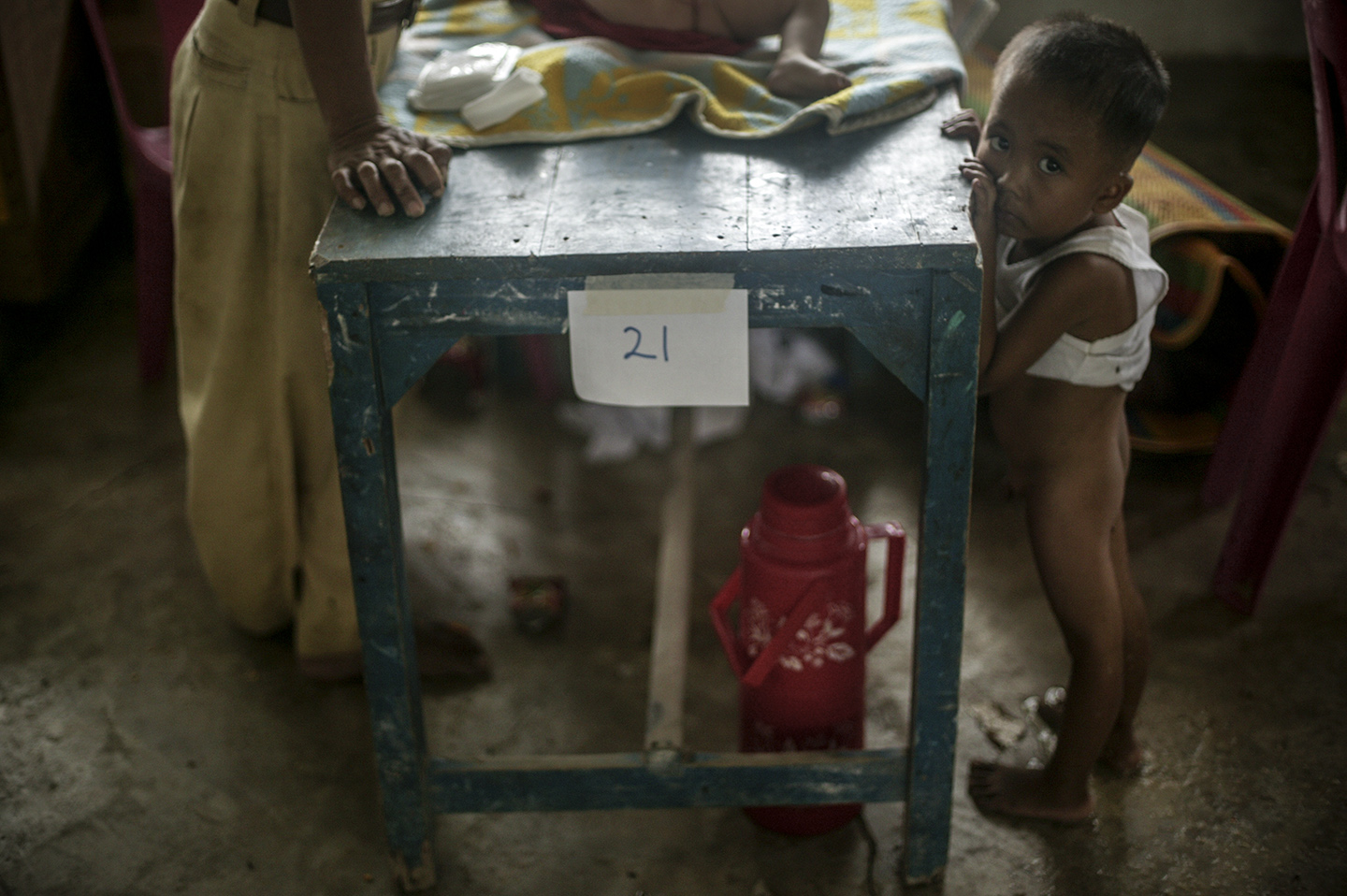A boy stands in his own diarrhea as he waits for treatment.