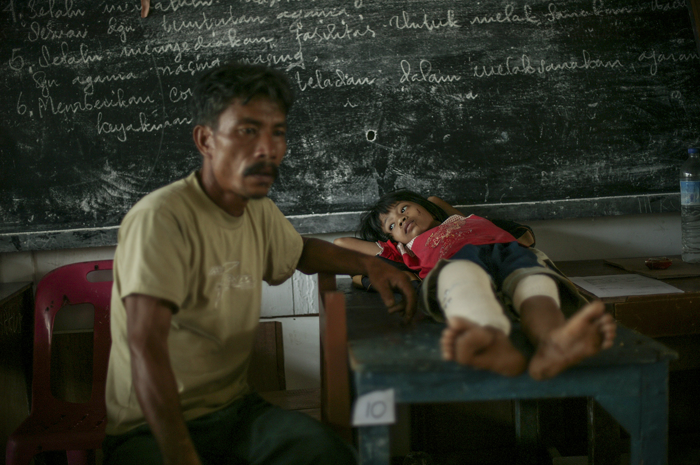 A father next to his injured daughter at a makeshift hospital where they wait to be evacuated.