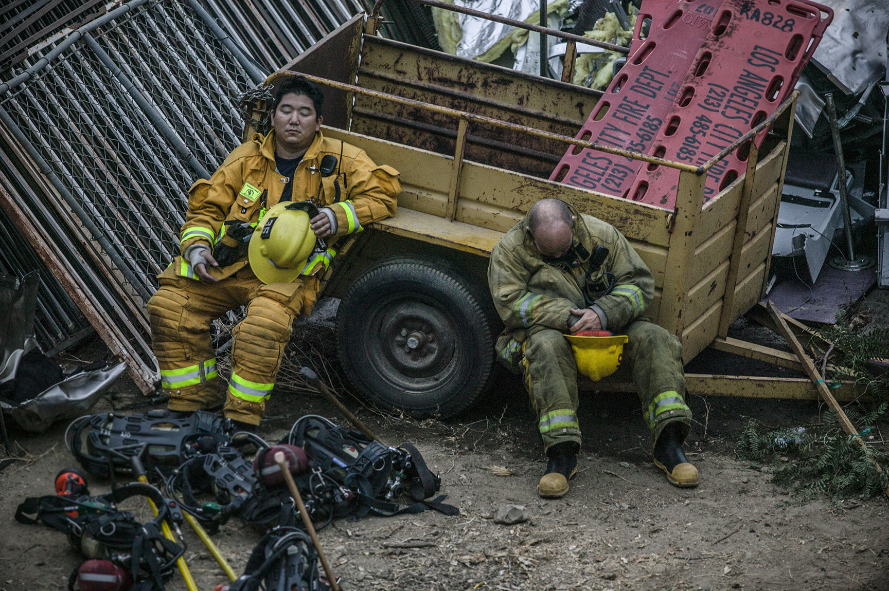Exhausted firefighters find a moment of rest at the scene of a deadly train crash where 25 people lost their lives.