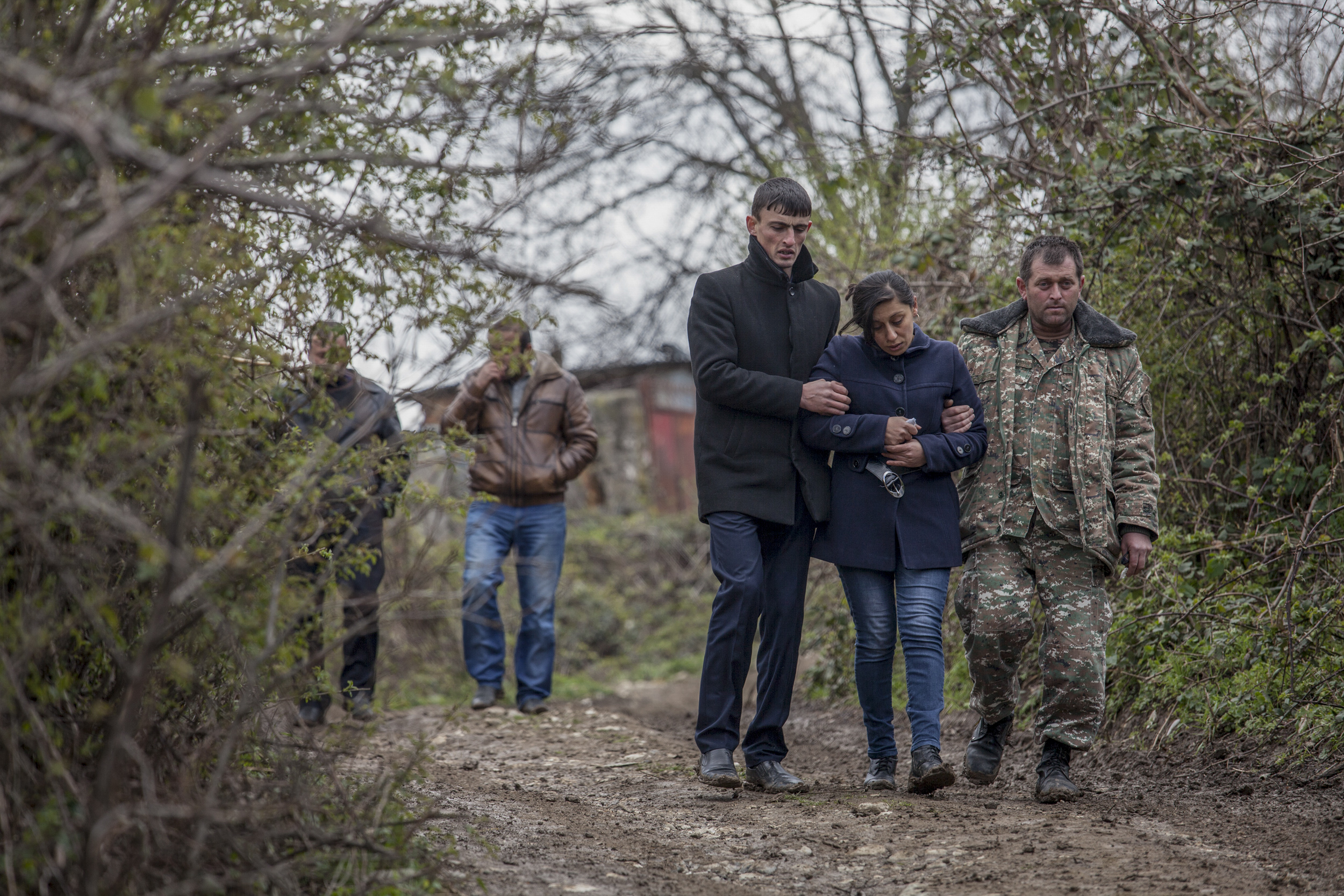 The mother of 12-year-old Vagharshak Grigoryan is escorted by her husband, right, after the boys funeral. The boy was killed when Azeri Grad rockets hit their village during the first day of fighting on April 2.