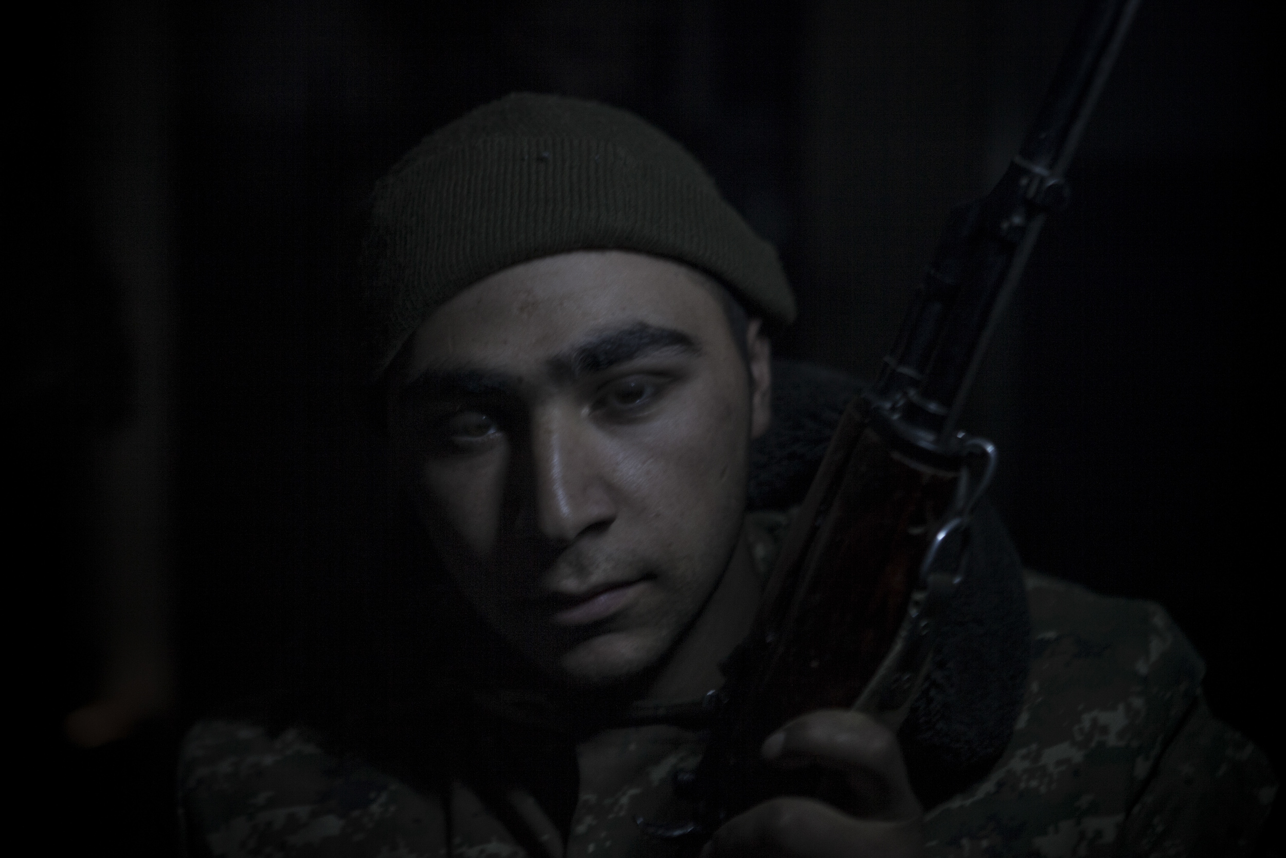 Soldiers awaiting orders in darkness, lit only by kerosene lanterns, at a military base in Mataghis, Karabakh on April 5.