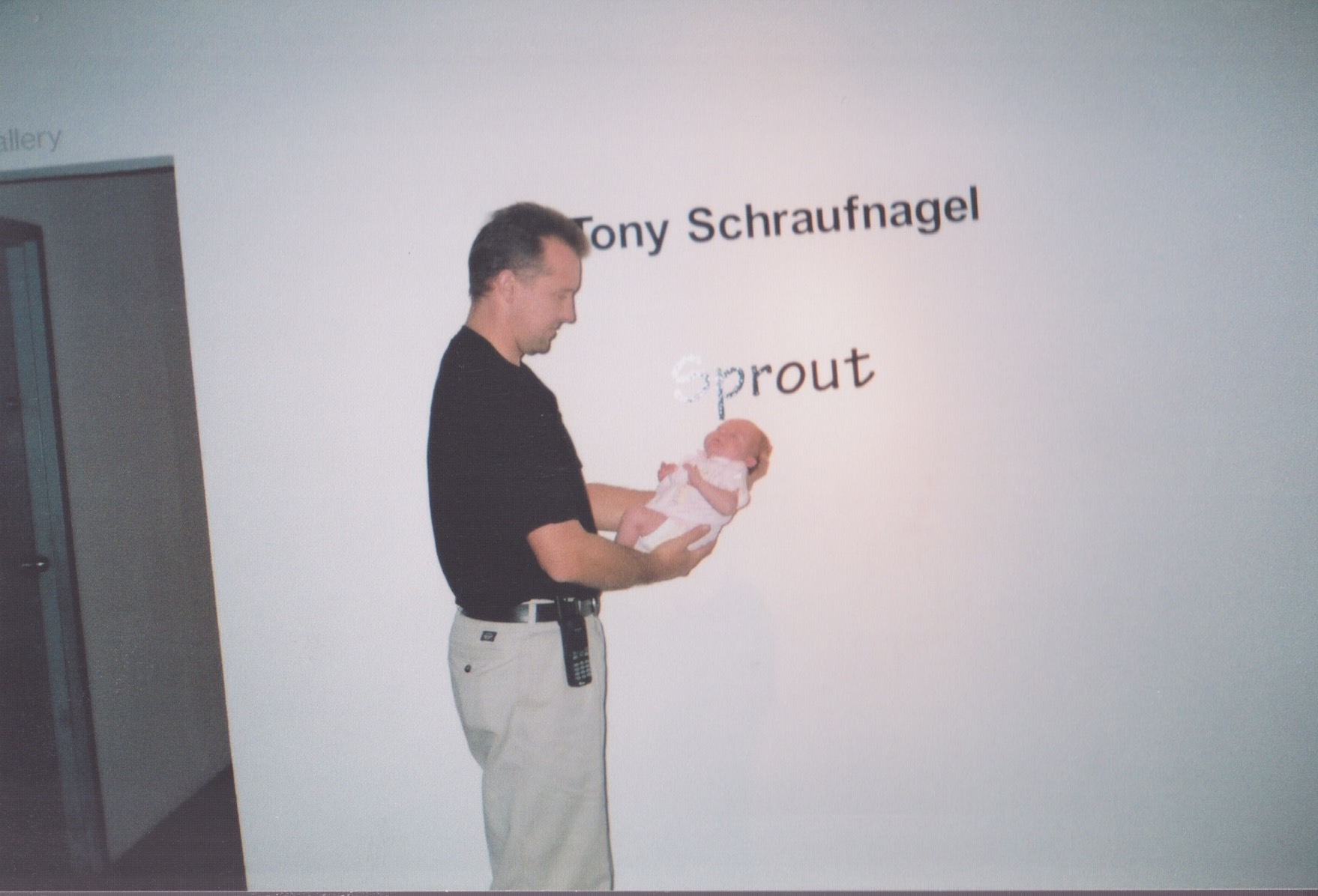 Tony Schraufnagel at his solo exhibition, Sprout, holding his eldest daughter one week after she was born.