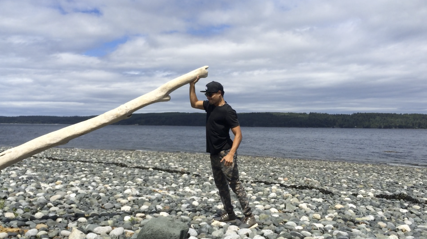Thosh Collins using drift wood for weight resistance while visiting Alert Bay, BC, Canada.