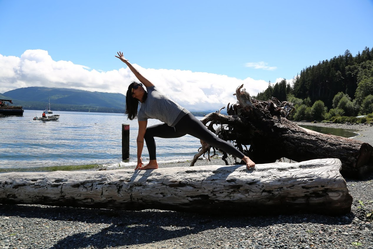 Yoga therapist Jessica Barudin practices yoga on a log, recognizing the importance of exercising in nature.