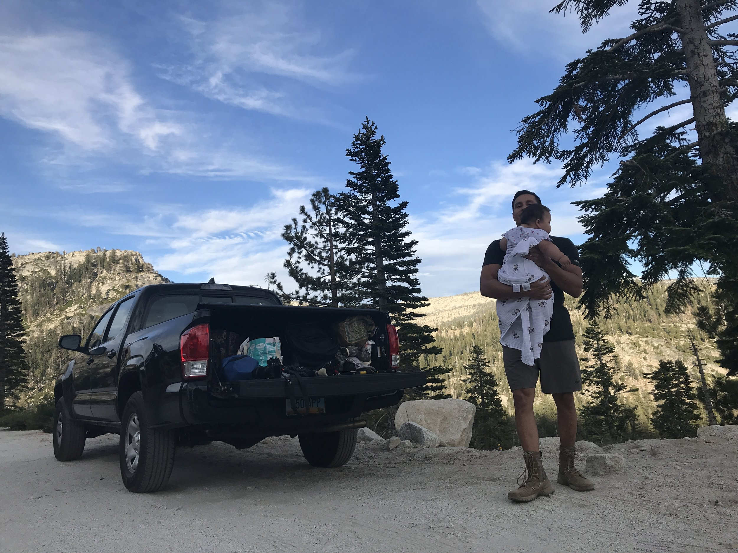 Thosh holding baby after a tailgate diaper change overlooking an epic mountainside view in Yosemite.