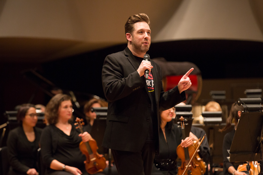 Brett Mitchell addresses the audience before a performance of  Jurassic Park – In Concert  with the Colorado Symphony in May 2018. (Photo by Brandon Marshall)