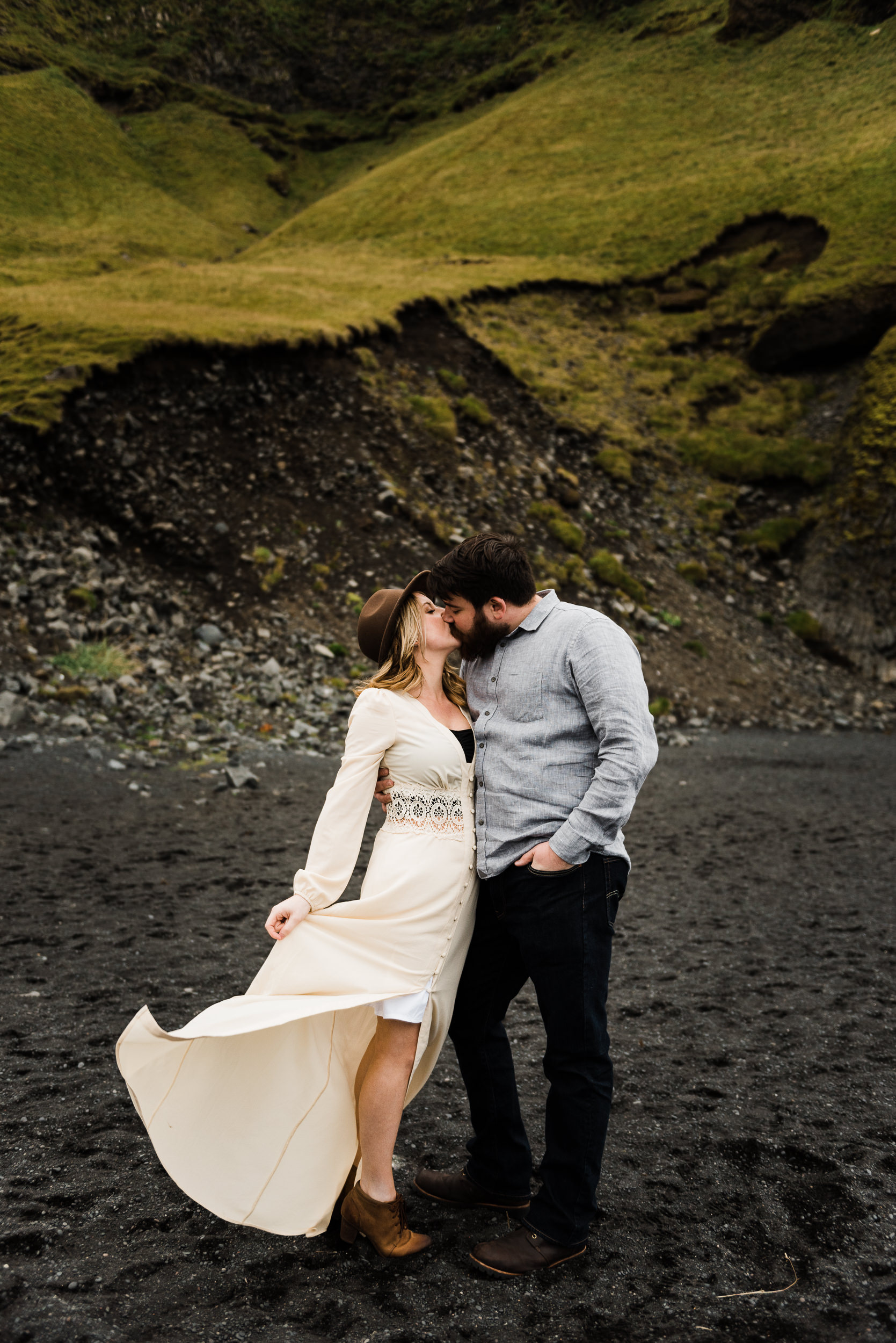 A couple on their honeymoon in Iceland, stand side by side, kissing, hands around each others' waists. Black sand below them, lush grasses behind them on the rocky hillsides. A woman at left, wearing a flowing off-white dress, hat, and boots. A man at right with beard, wearing a buttoned shirt, jeans, and boots.