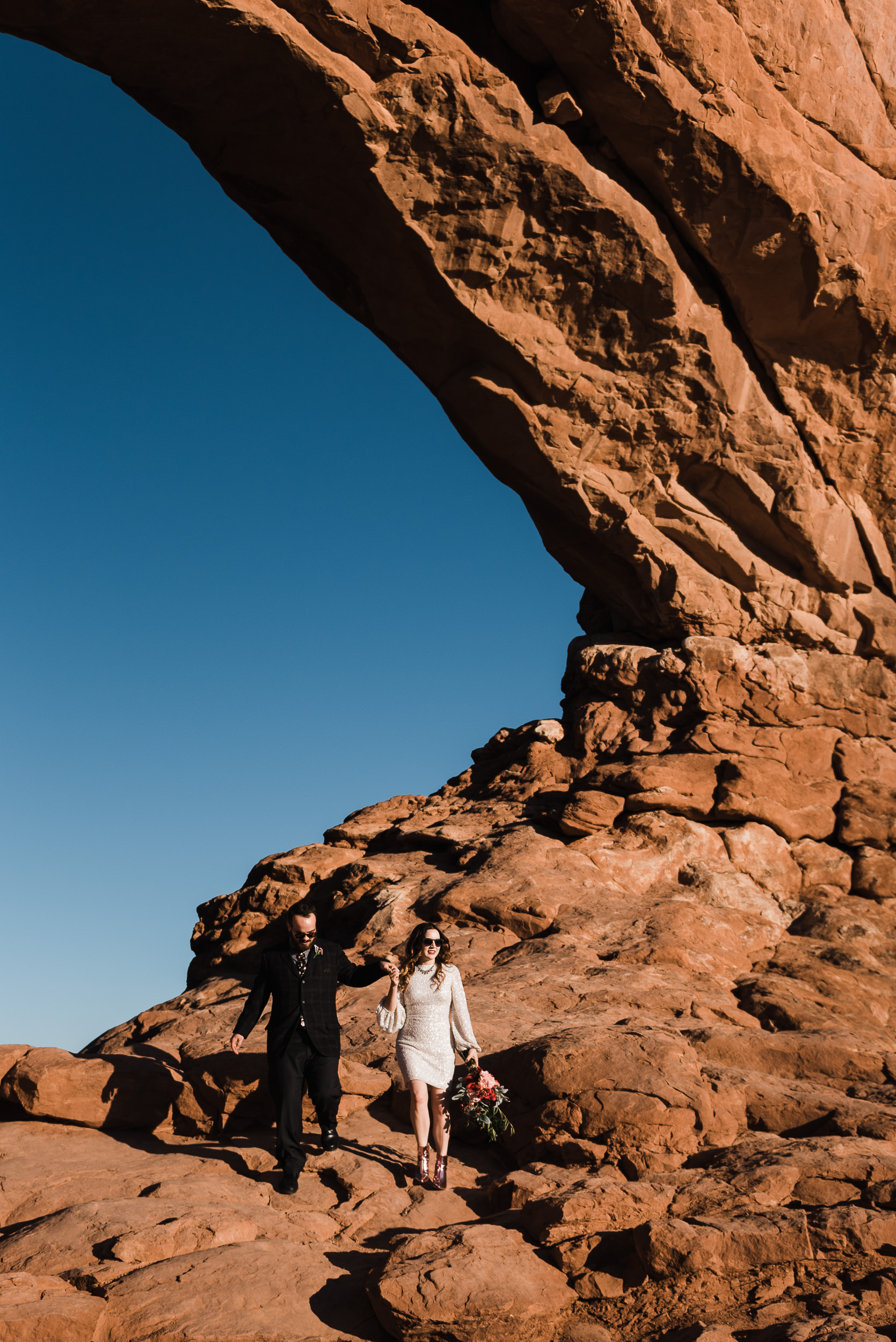 An elopement couple walk down away from a dramatic arch in Arches National Park in Utah. The bride holds her husband's hand over her shoulder, leading the way, bouquet in the opposite hand. They're both wearing sunglasses. The dramatic arch reaches very high above them.