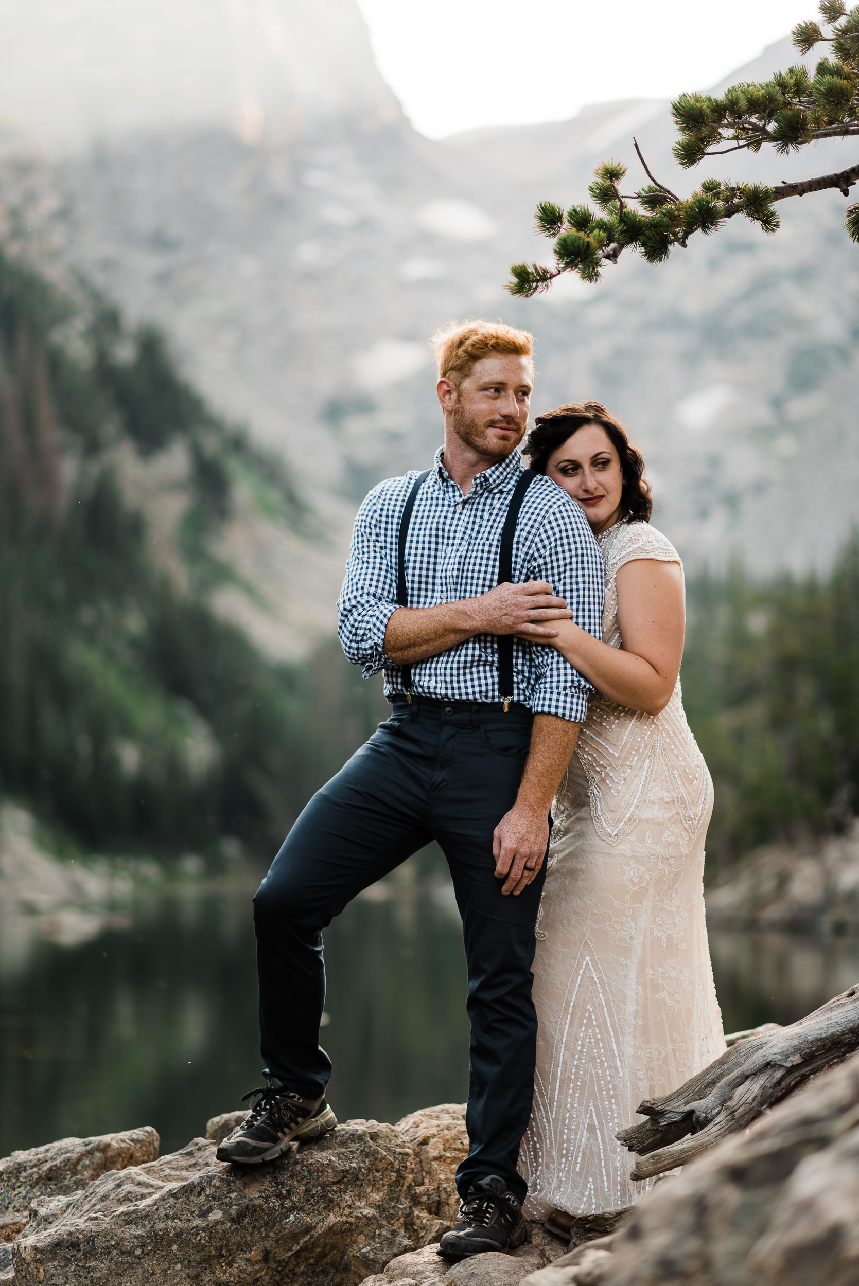 A couple hold each other close in Rocky Mountain National Park. They were married earlier in the day somewhere else in the park before hiking out. Their perched on a rock, a tree branch overhead, a lake reflecting the trees and dramatic peaks behind them.