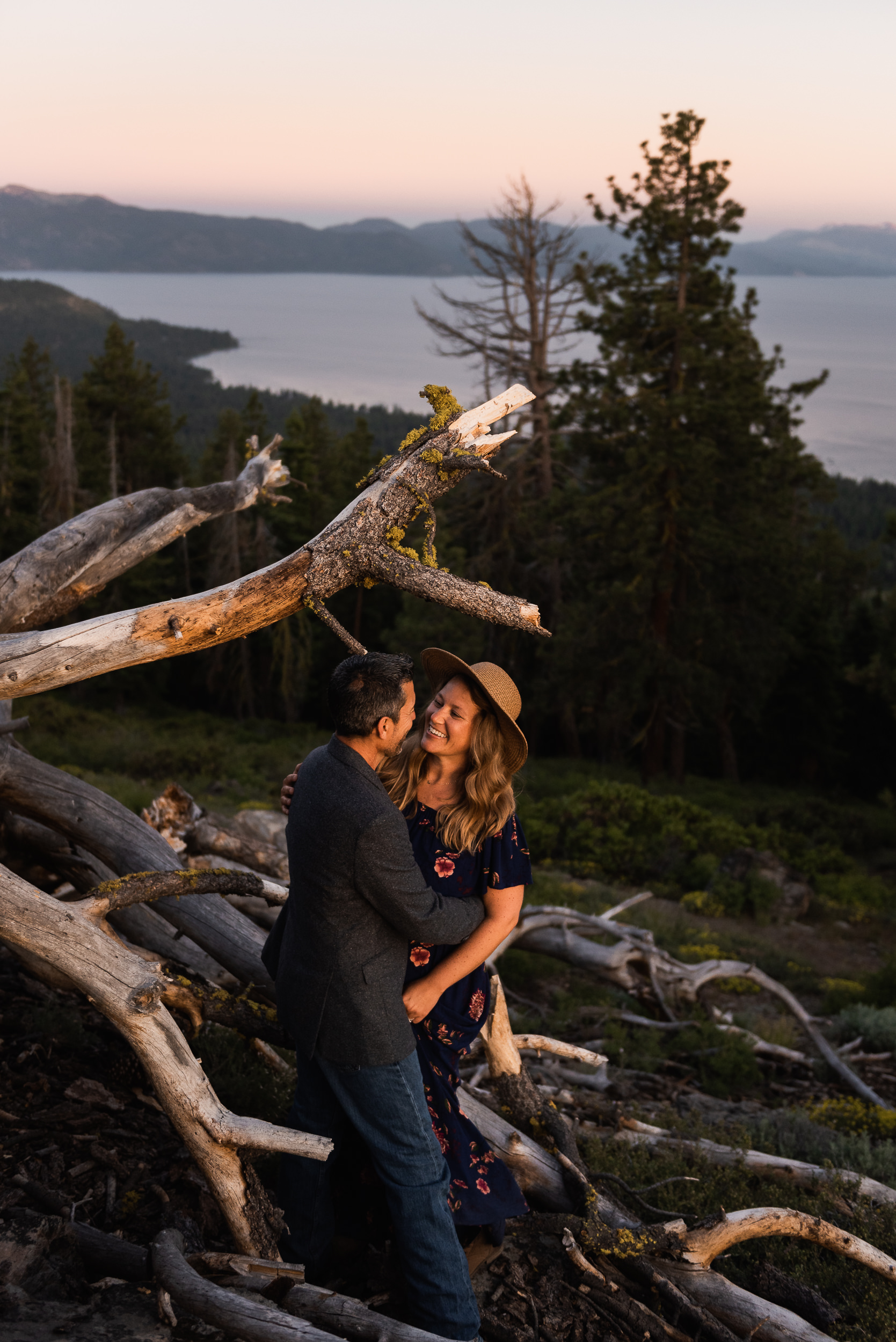 A couple looks each other in the eyes, smiling big, holding each other close. They're high on a hillside overlooking Lake Tahoe during an anniversary session. They're tucked up near a fallen tree, whose branches like tendrils crawl this way and that. Trees, mountain, and Tahoe are in the background.