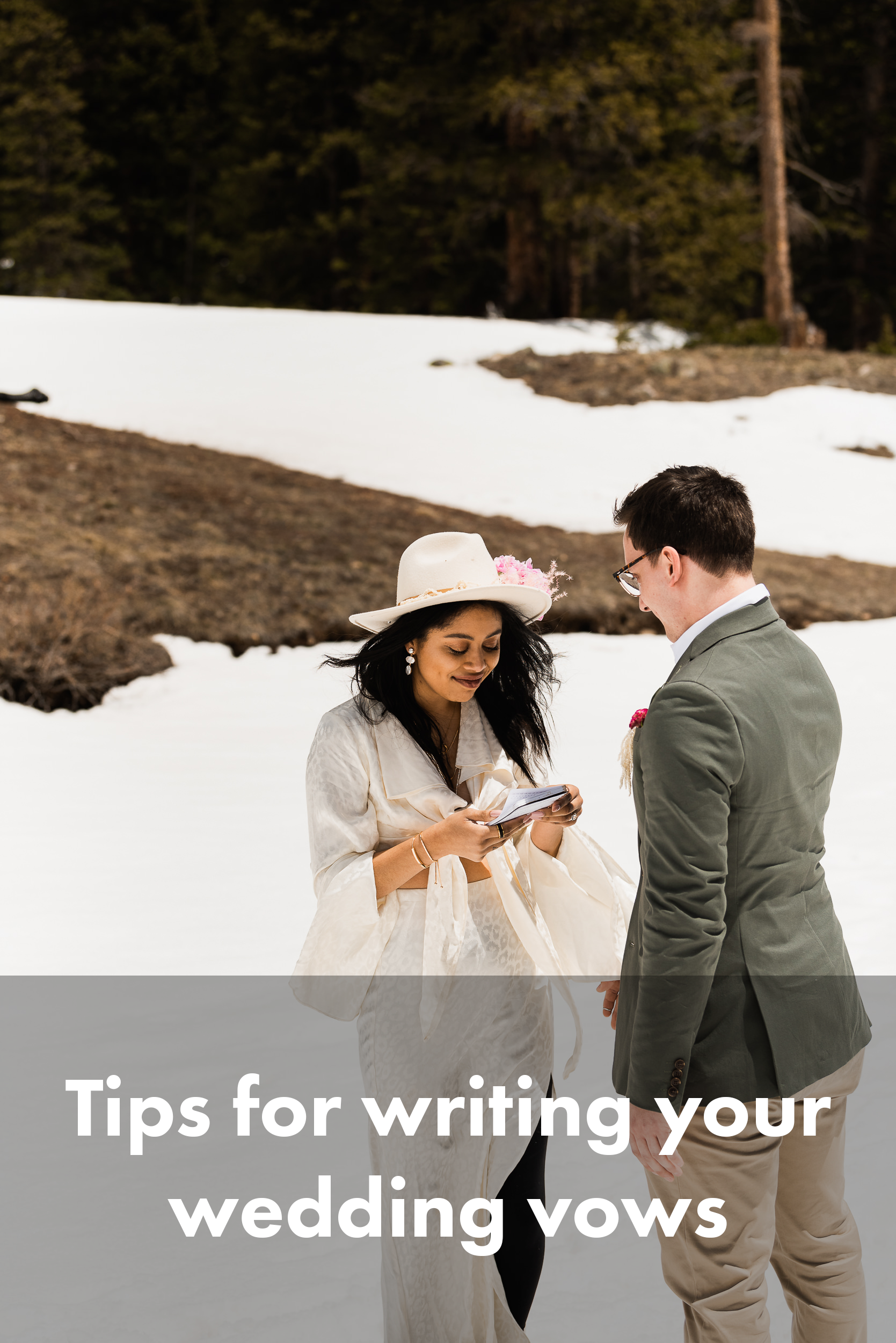 Here's an elopement couple during their ceremony – the bride is smiling and looking down at her vows as she reads them. She's on the left, her groom on the right. She's wearing an airy collared blouse, a hat with a flower in it, and leggings with hiking boots. The groom is wearing a blazer with chinos. Snow is all around them, with trees in the background.
