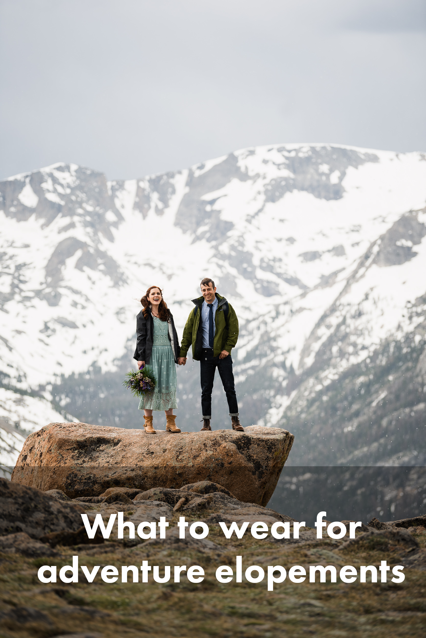 A bride and groom stand side by side on a large flat rock, framed by dramatic snow-covered peaks. They're holding hands, the bride holding flowers and the groom with his thumb in his pocket. The bride on left is wearing a calf-length dress and boots, with a jacket over her dress. The groom is wearing a buttoned shirt, tie, cuffed jeans, and boots, along with a jacket. The wind is blowing, it's cold, but they're laughing.
