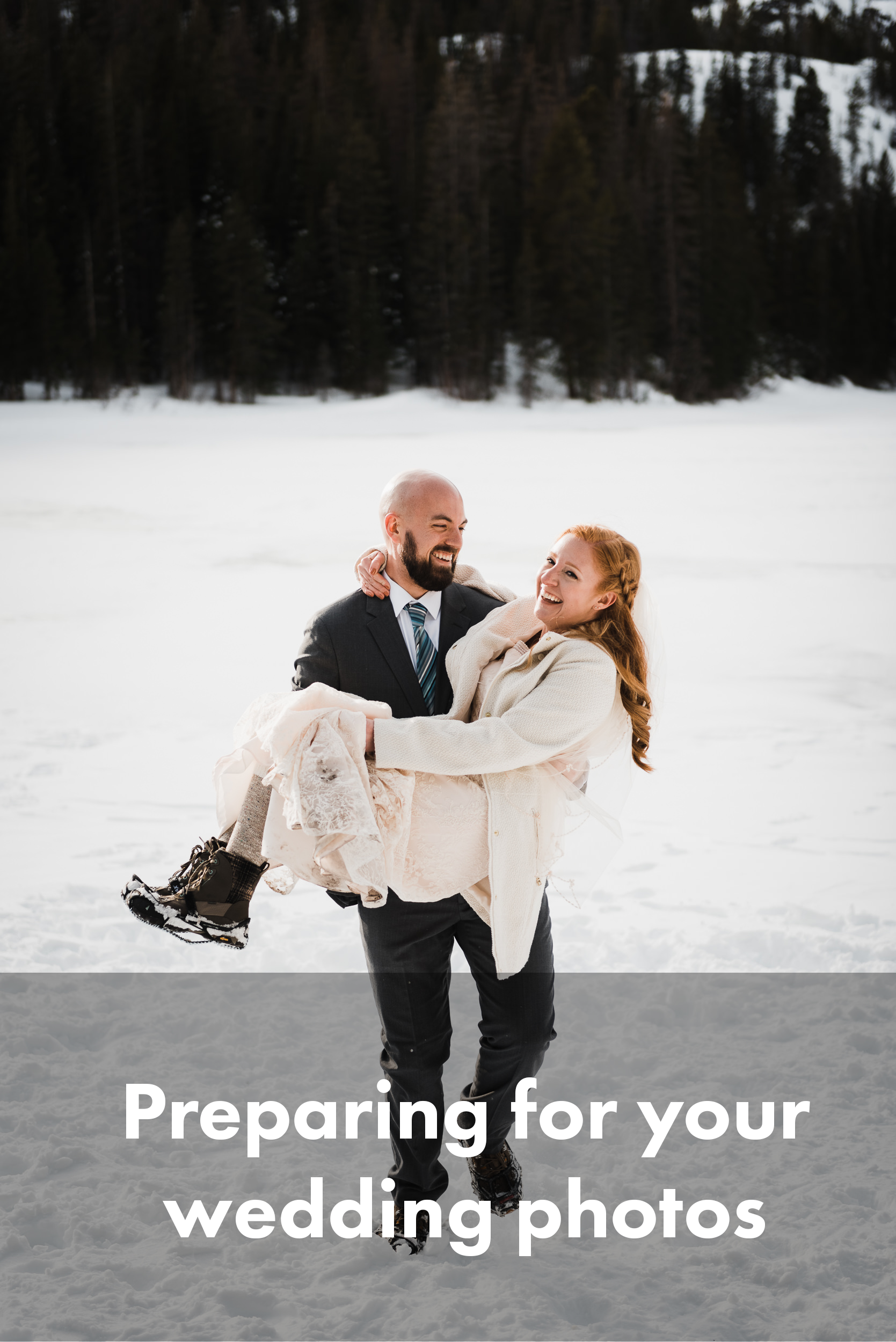 A groom is carrying his bride, standing on a frozen lake in Colorado. The groom's wearing a suit with hiking boots, traction cleats. The bride is wearing a dress with hiking boots and cleats, with a warm coat on. They're both laughing, and the groom's walking with her in his arms. Tall trees are in the background.