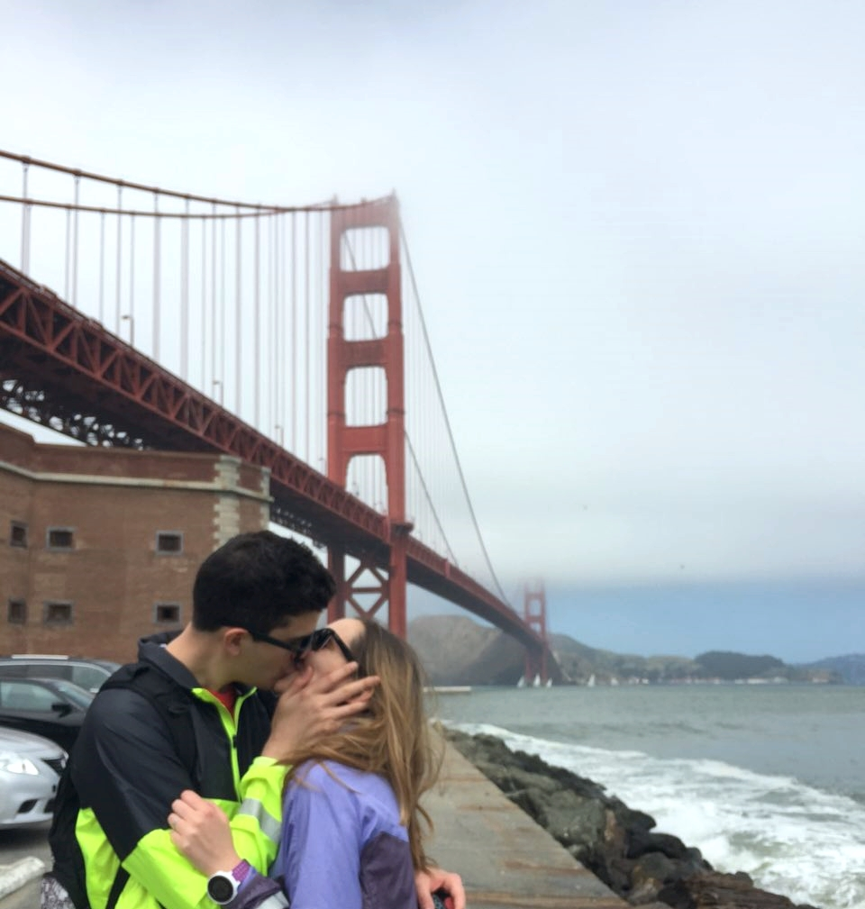 Beso con cortavientos reflectantes y Golden Gate Bridge de fondo