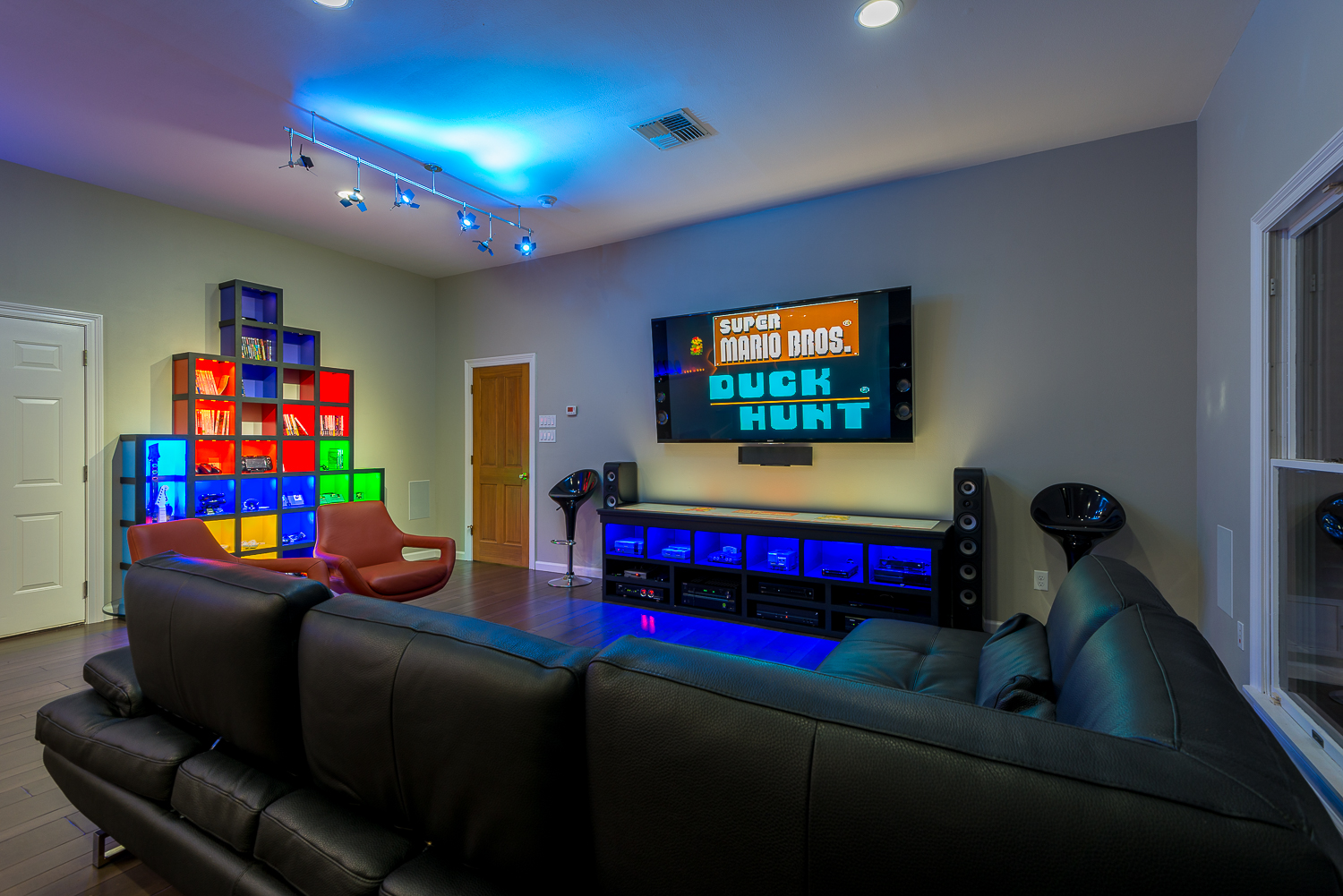 "This family's arcade room features 6 generations of gaming devices, from NES to XBox One.  The ""Tetris Wall"" storage shelf and custom media console were built by Josh Hebert at Marlin Construction of Houma, while DJ Chauvin of First Circuit provided all of the tech lighting."