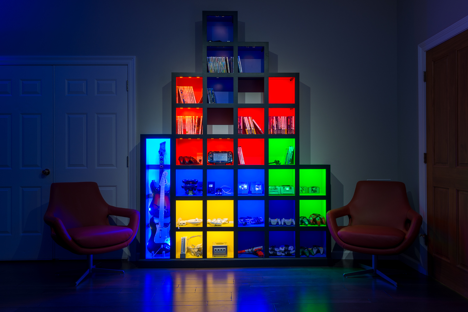 "The room's ""Tetris Wall"" stores all of the controllers, gaming discs and cartridges."