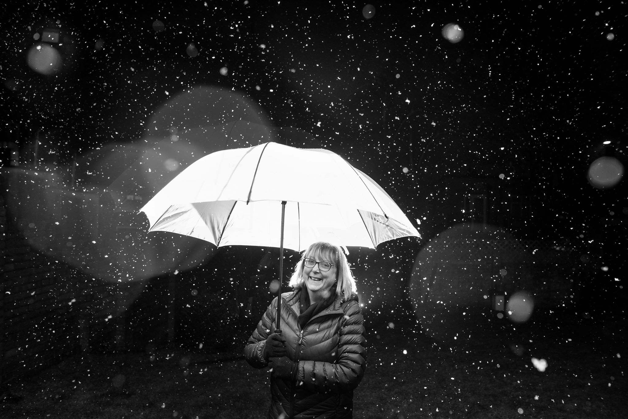 """""""Last January I was getting to grips with and improving my off camera flash so when I saw it was snowing I grabbed my camera, speedlight and triggers and the closest person (mum) and did this super quick shot. I love the snow flakes, the droplets on the lens doing lovely bokeh stuff, but mostly I love her beaming smile - ever supportive, ever proud. I wouldn't be where I am today without her and my dad. They're awesome and I love them""""  Elyse Marks"""