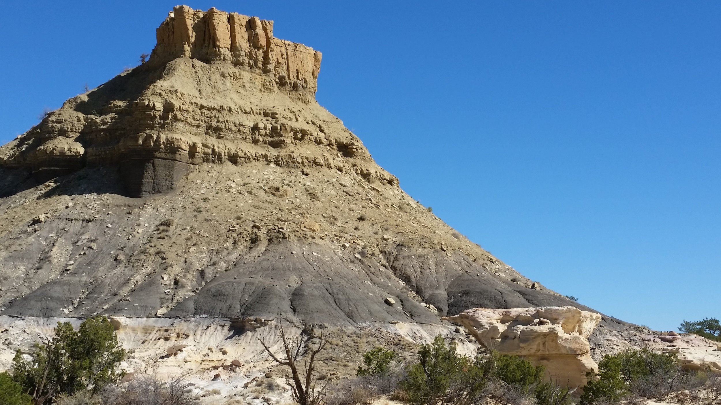 A butte of bentonite hills with a sandstone cap.