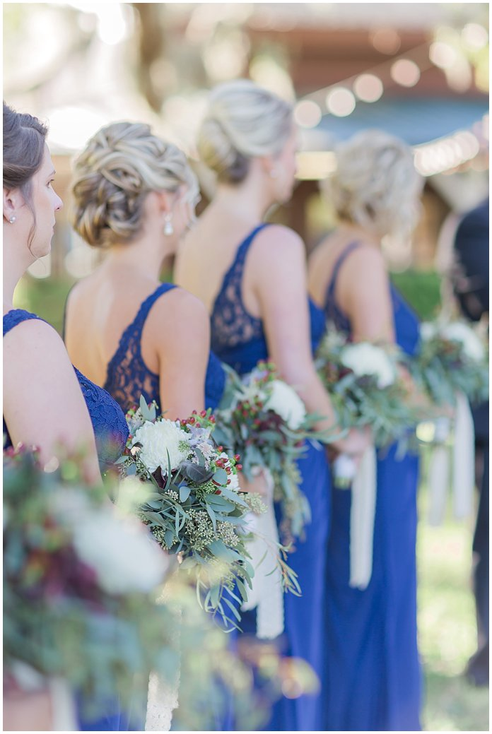 Navy Bridesmaids Dresses and white bouquets with berries