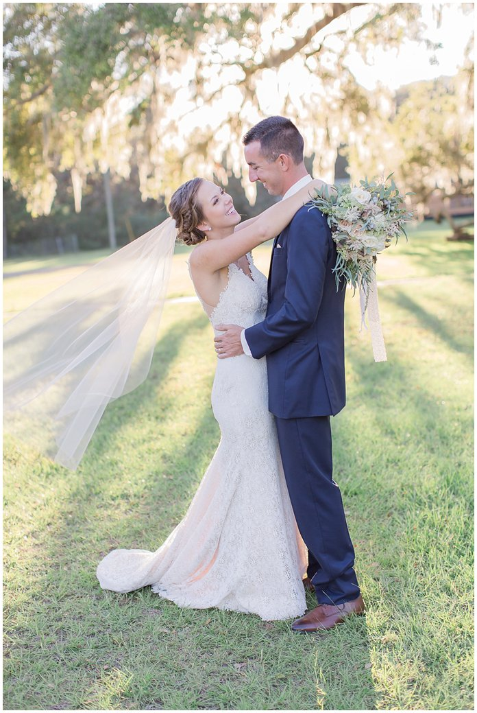 Bride and Groom Portraits under giant oak tree with flawy veil