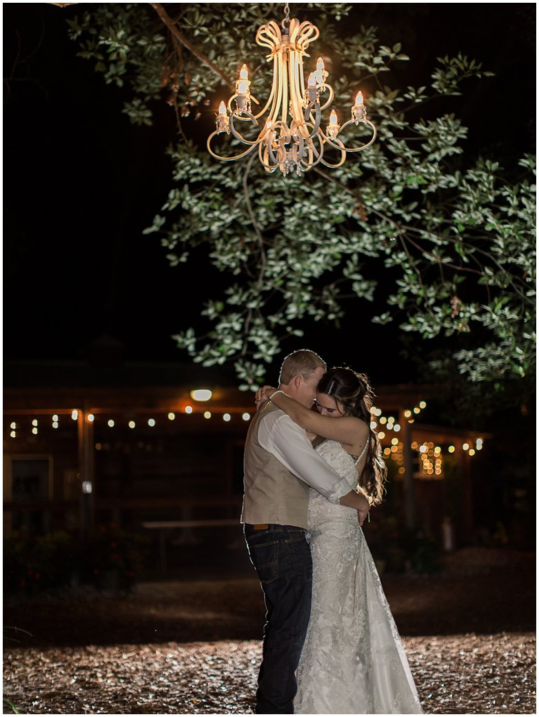 Bridle Oaks Bride and Groom Posing Under Chandelier at Night