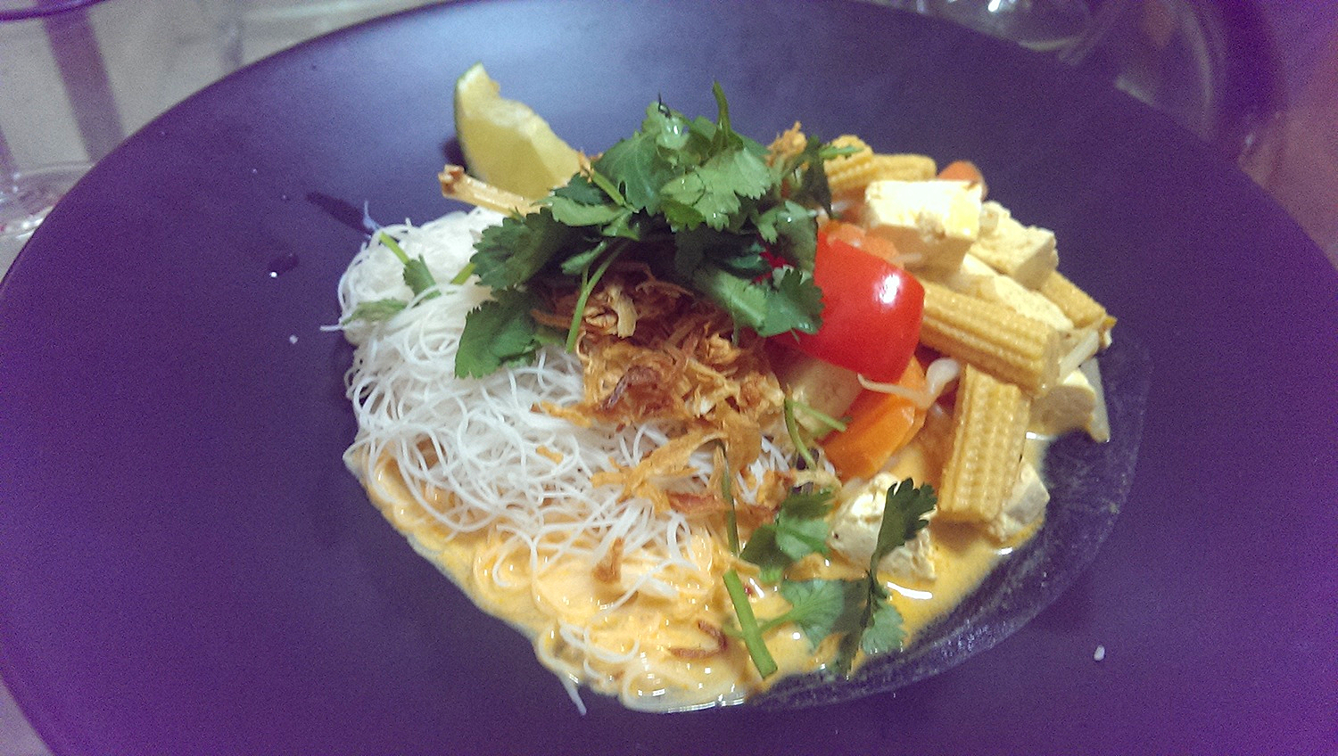 Vegan variation of laksa with rice vermicelli and thai red curry paste. Including tofu, baby corn, carrot, red pepper and a fried onion cilantro topping.