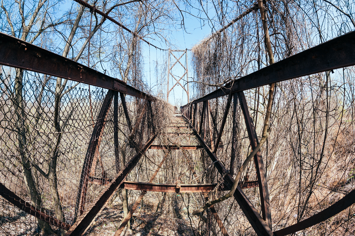 This use to be a pedestrian suspension bridge that connected two feuding neighborhoodsof different cultures, and during a riot thewooden walkway was burned. Now it's just the rusted skeleton over a deep ravine, which I wasn't about toscramble over.