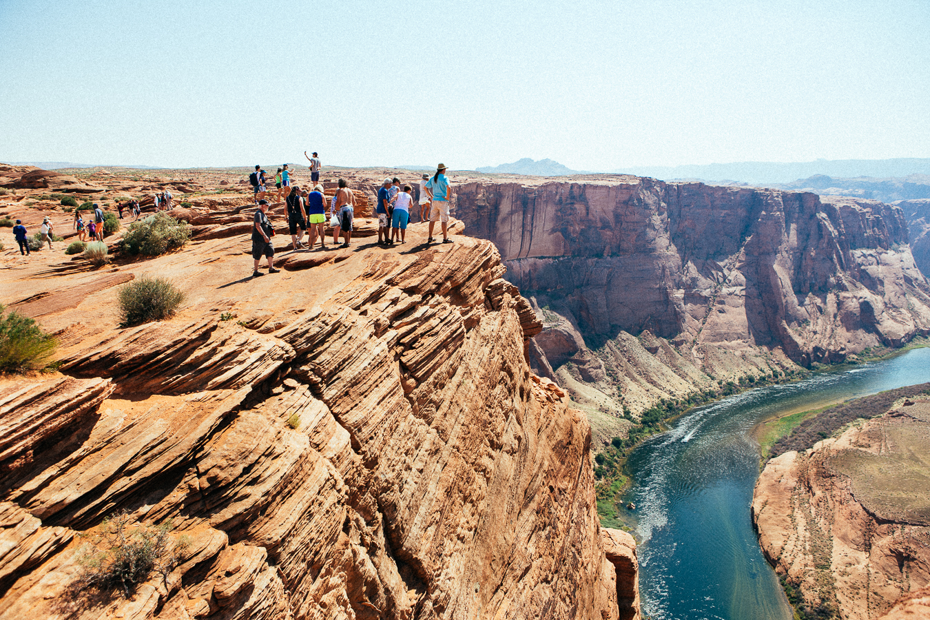 Near Lake Powell is a point where the Colorado River wraps a 270º curve, called Horseshoe Bend. It's a fairly easy hike to view it, which brings hundreds of tourists to this 1000' cliff where you can get right near the edge...