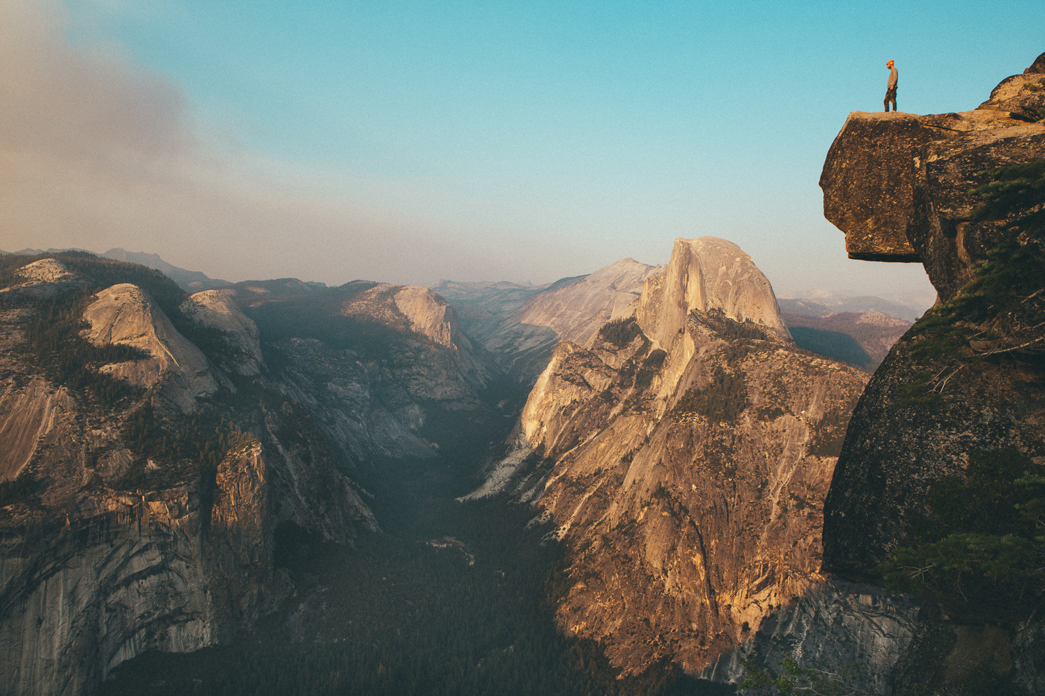 Off the main path at Glacier Point is a highly unadvised trail to the cliff's edge. (...skateboarders often turn a blind eye to the rules)At sunset I placed my camera and tripod a couple feet from the drop, snapping this breath taking self-portrait with the last light hitting Half Dome off in the background.