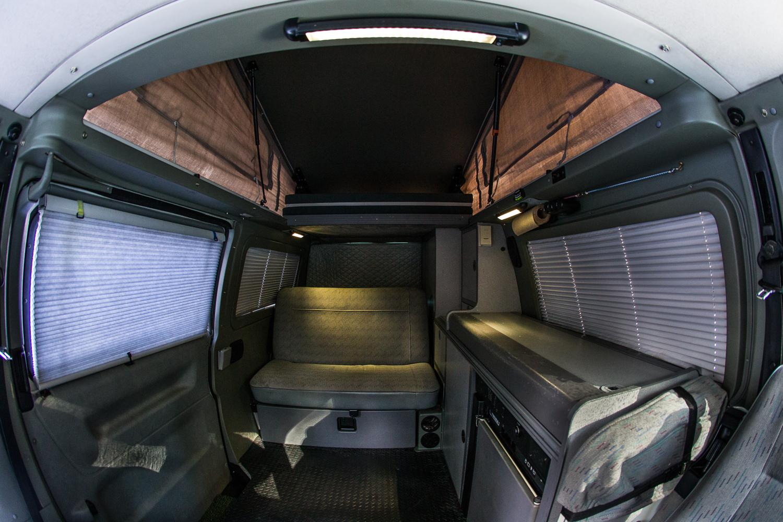 Upper bunk platform slides back for convenience. Side windows have privacy blinds. Also included are custom bug screens for sliding side door, back door, &front windows.