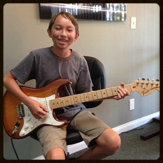 My son picked up a guitar at age 8, and soon found his passion. So my husband started teaching him the basic chords and how to strum, and Marlin was soon playing songs. Although I don't know much about playing, I could see that my son needed professional instruction. We were referred to Marc by a friend, and visited him at his studio. To our delight, Marc is great with kids, having young children himself. He has the best balance of patience while giving excellent constructive correction, in a positive way. During the first lesson, Marc quickly identified several incorrect things Marlin was doing and made adjustments such as how to best hold his guitar and pick, and how to sit properly. He gave him the good habits that set him up with a strong foundation. Marc is a perfectionist in the very best of ways. He also makes learning fun. Marlin has progressed quickly because of Marc's teaching style. I know several other kids who take lessons elsewhere and, I can say with confidence, that Marc brings his students along further, and with a set of skills faster, than anyone else I have seen. Marlin is now attending Orange County School of the Arts in the Guitar program, at the age 12. We are so proud of our son and Marc is a huge part of his success.      Donna B.