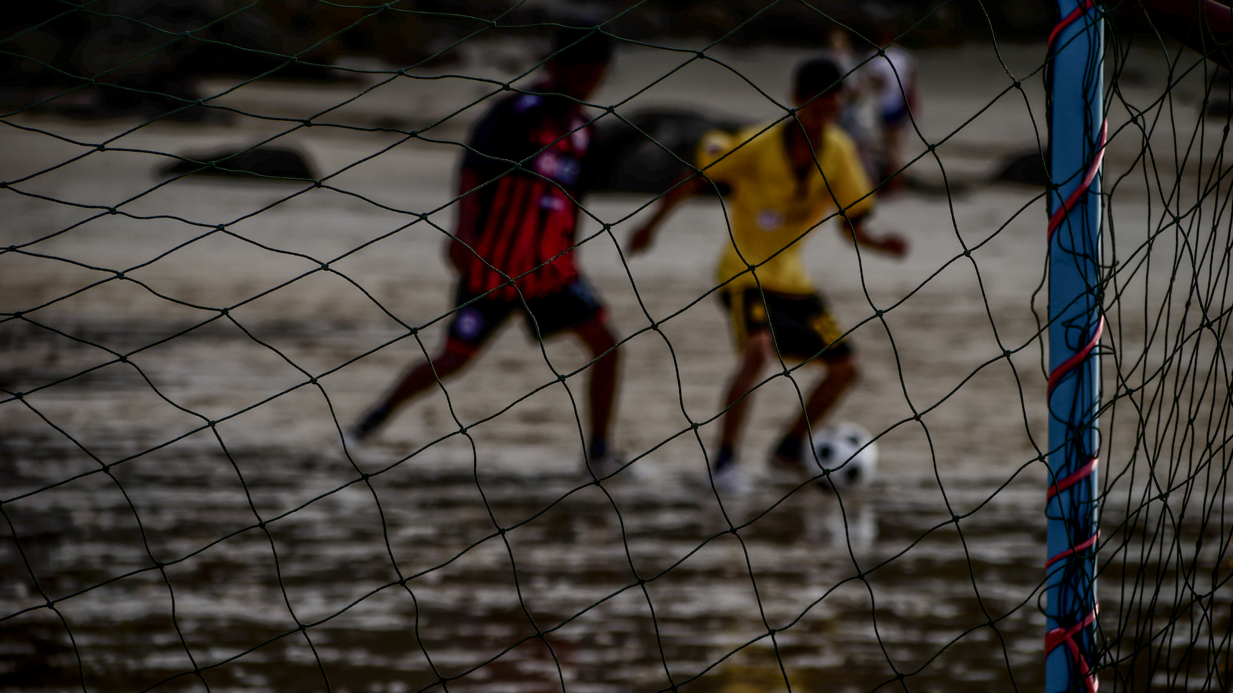 Fearless teenagers play soccer in the muddy beach of Phuket, Thailand