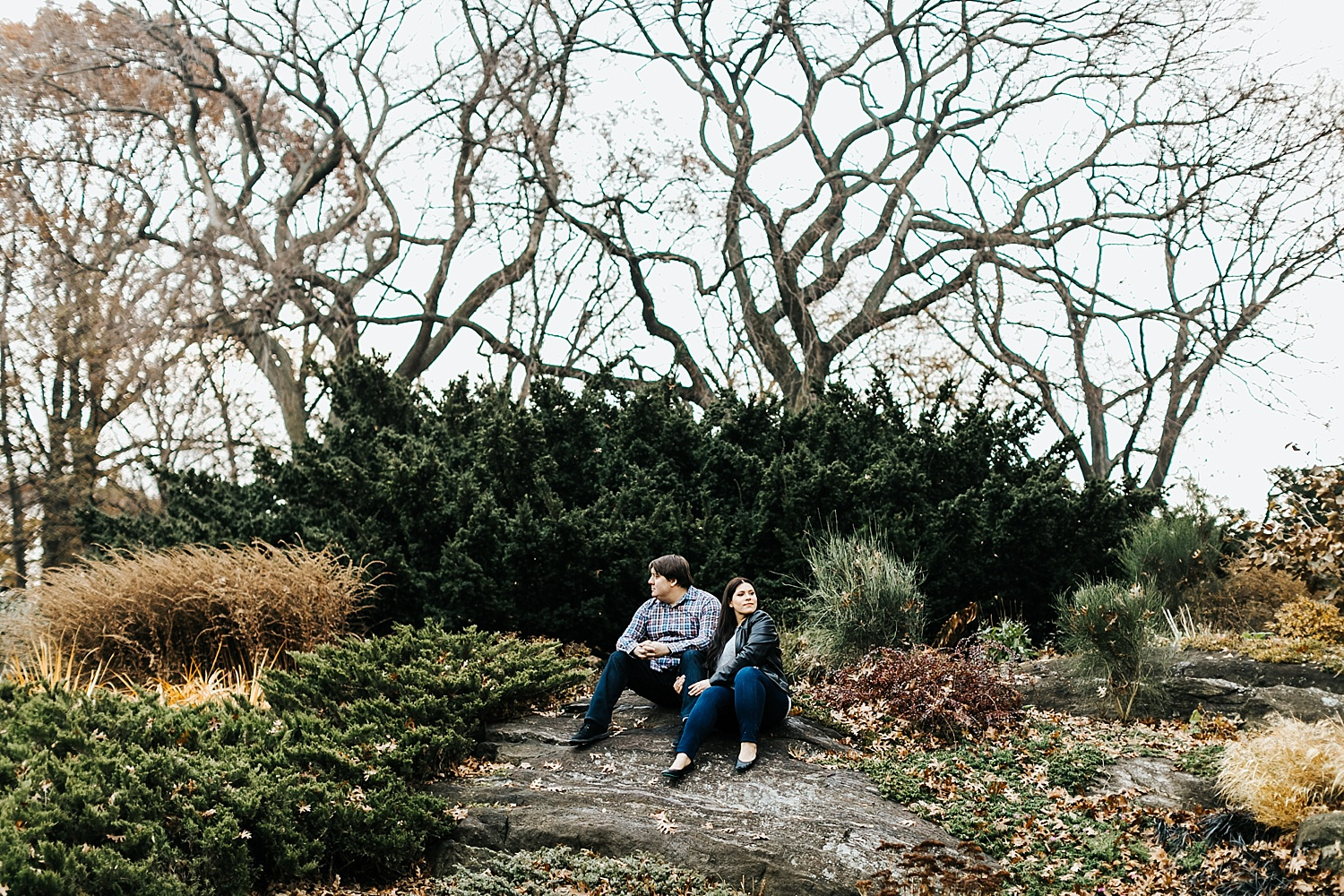 Couple sitting on a rock at fort tryon.