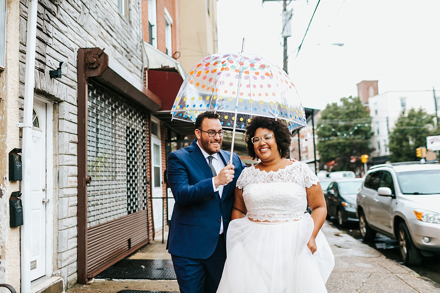 Bride and groom walking on a rainy day holding an umbrella in Philadelphia by Danfredo Photos + Films