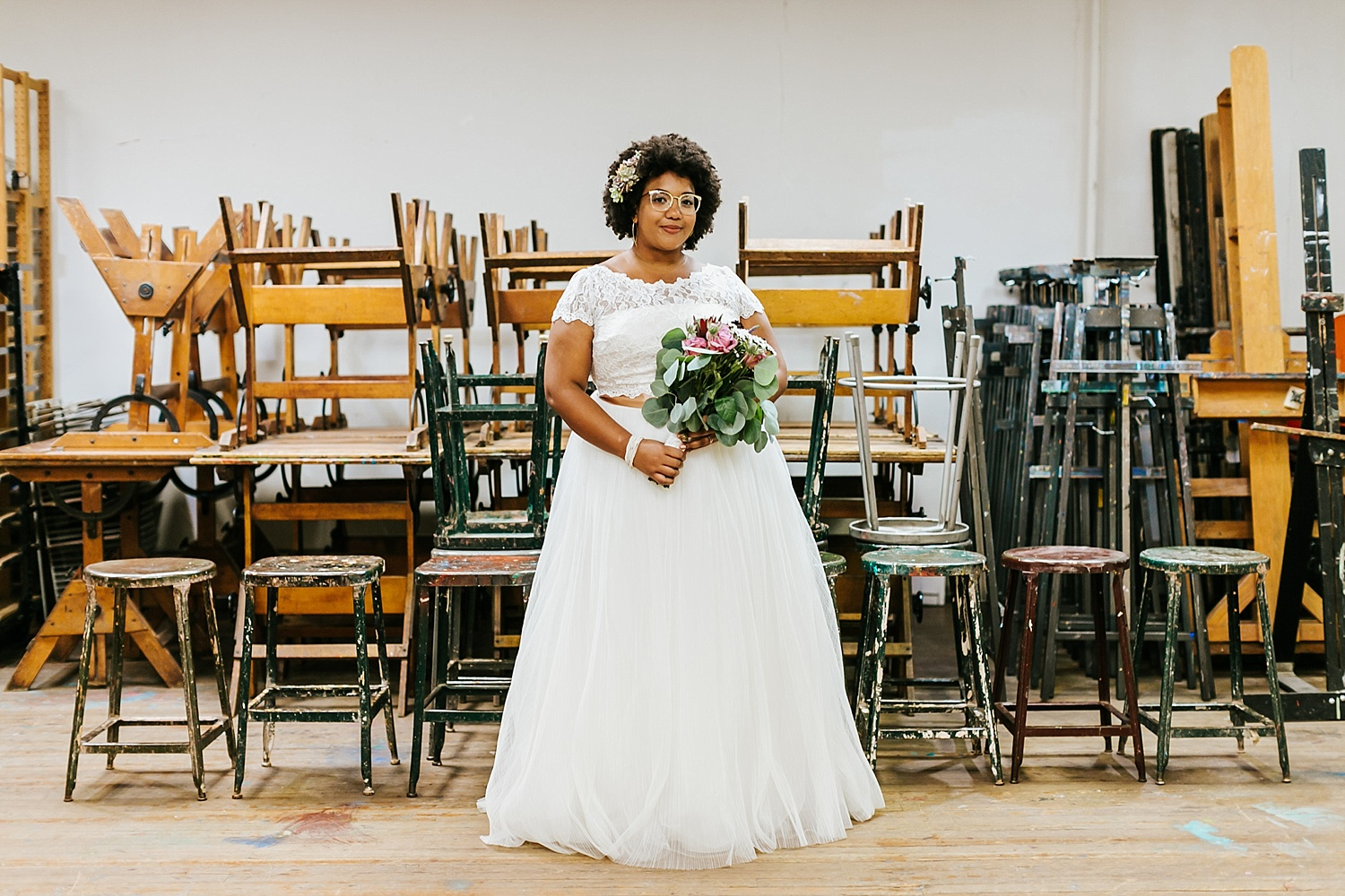 Bride holding a bouquet of flowers in a vacant class room full of chairs and art equipment at Fleisher Art Memorial