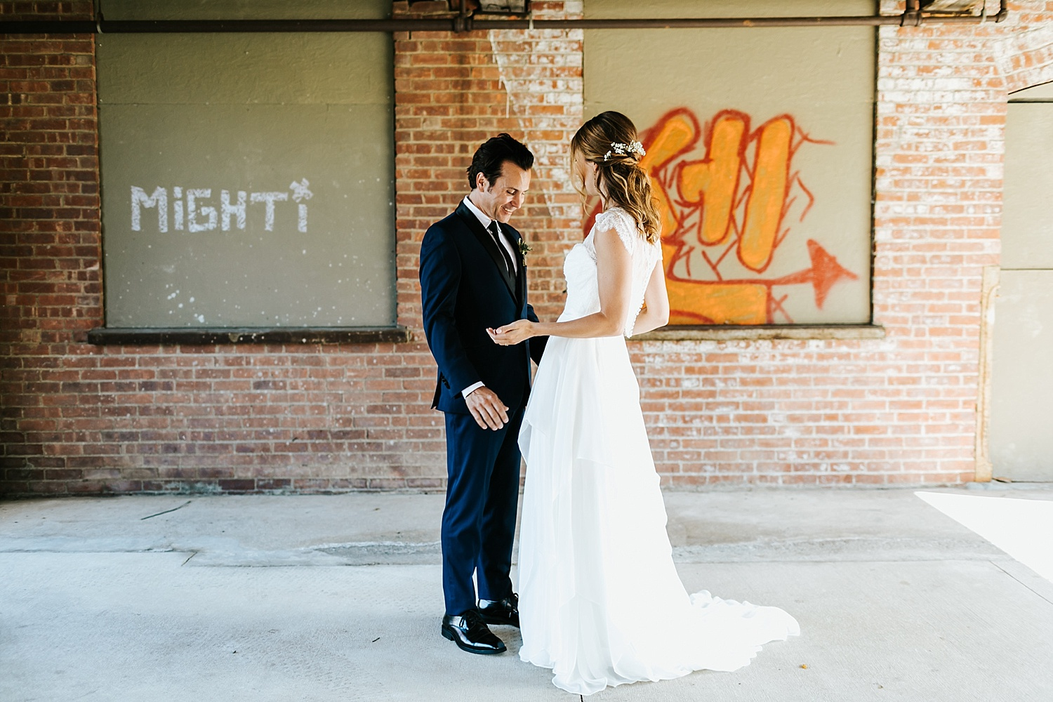 Bride and groom first look surrounded by walls full of graffiti