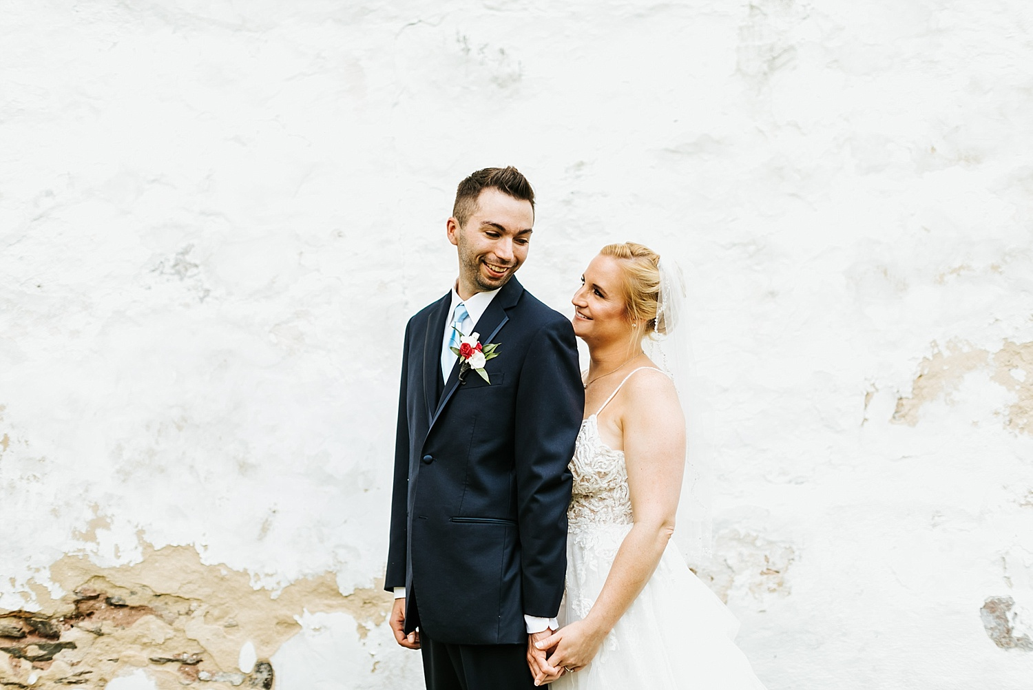 Groom looking over shoulder at his bride, holding hands on front of a white concrete wall.
