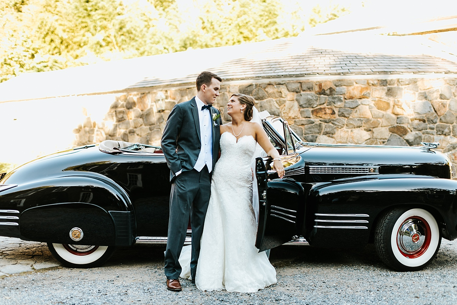 Bride and groom looking at each other in front of a vintage car