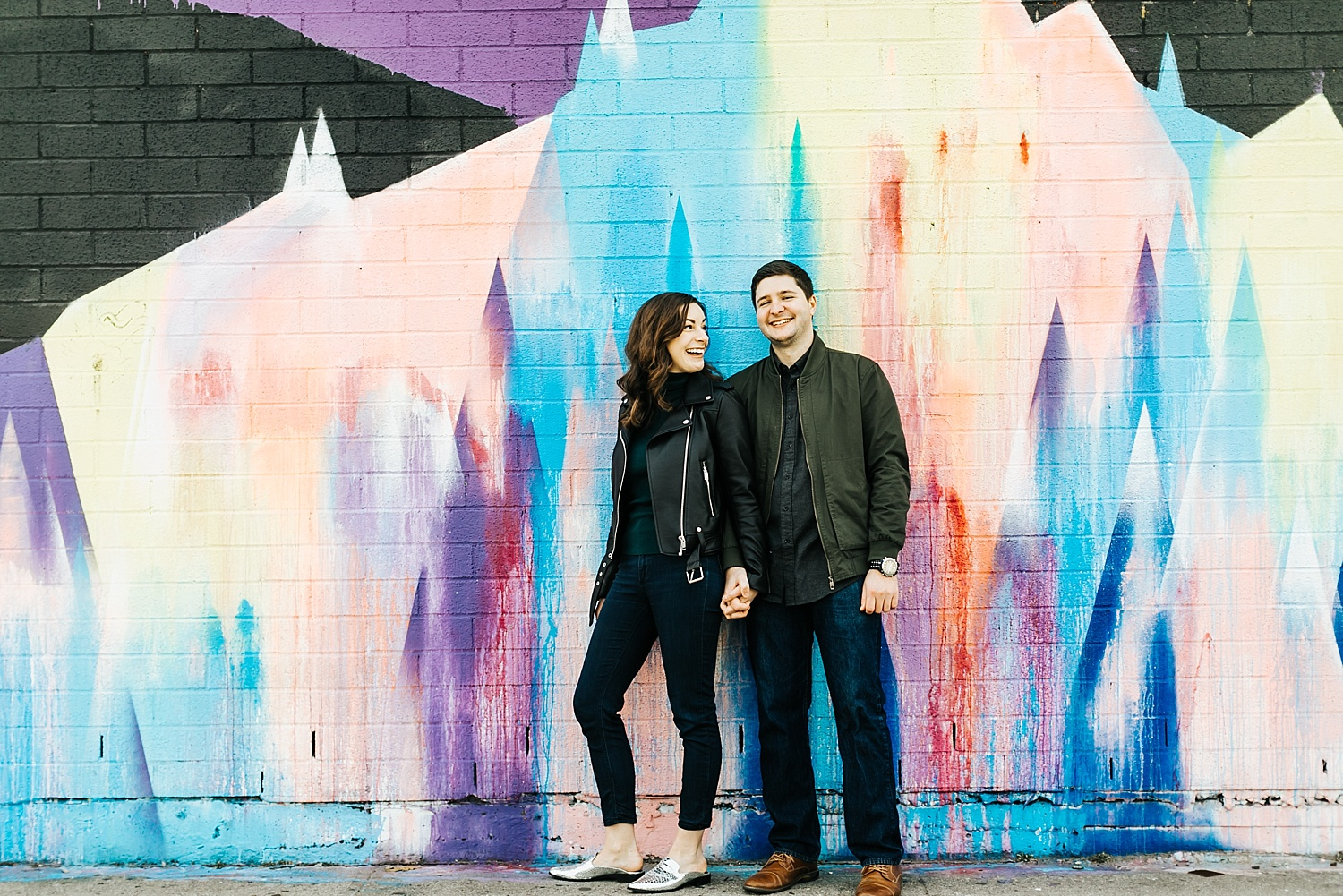 A couple holding hands in front of a mural in Brooklyn, NYC.
