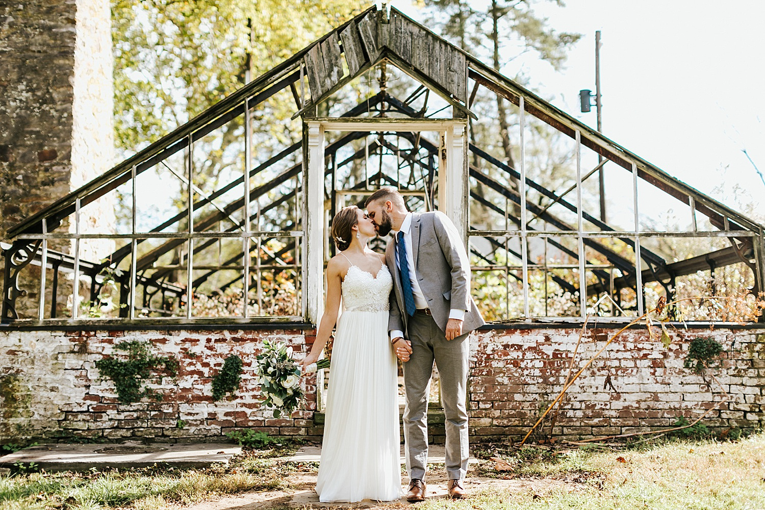 Bride and groom kissing in front of an abandoned outdoor plant nursery in philadelphia.