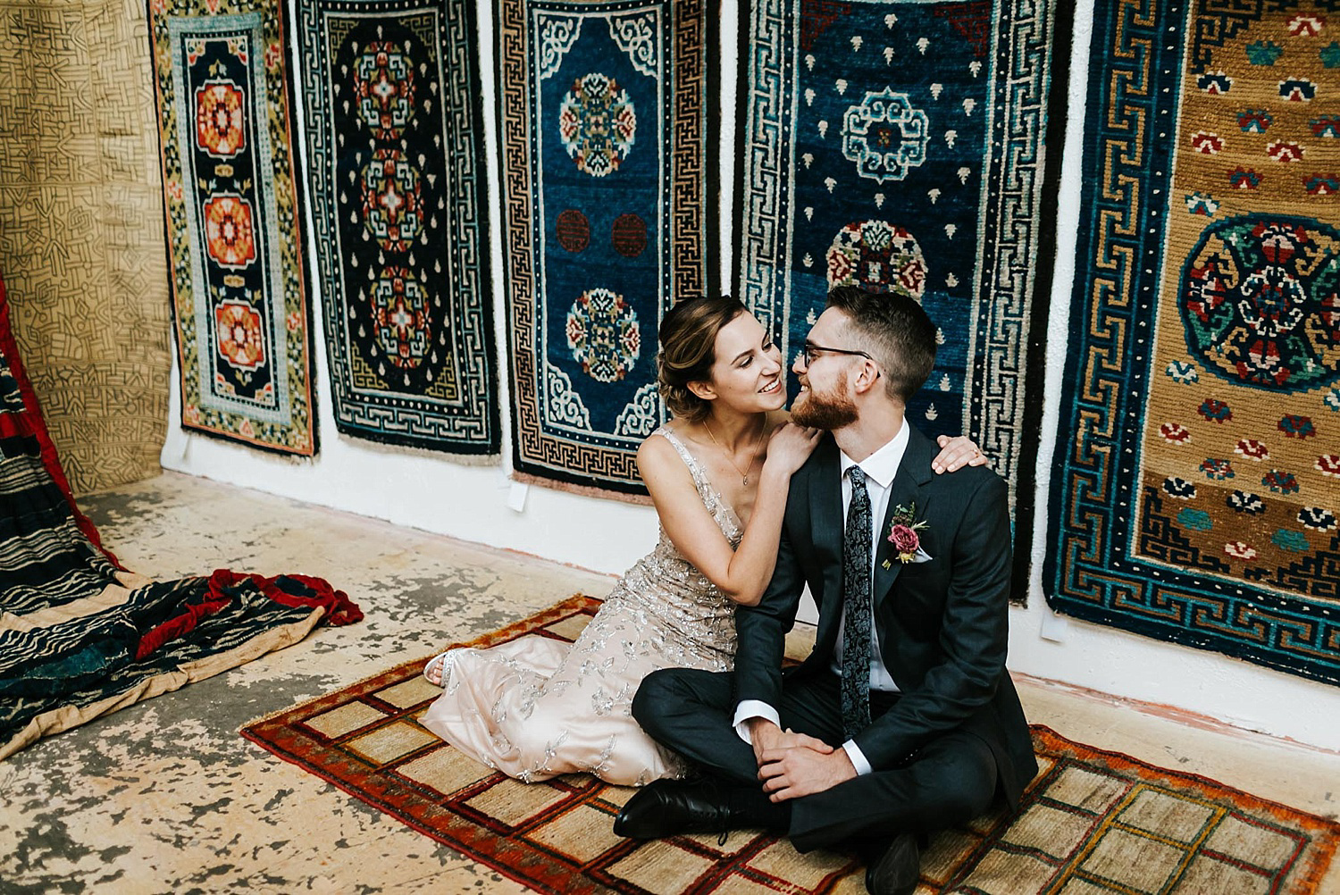 Bride and groom sitting on a vintage rug and surrounded by other rugs.