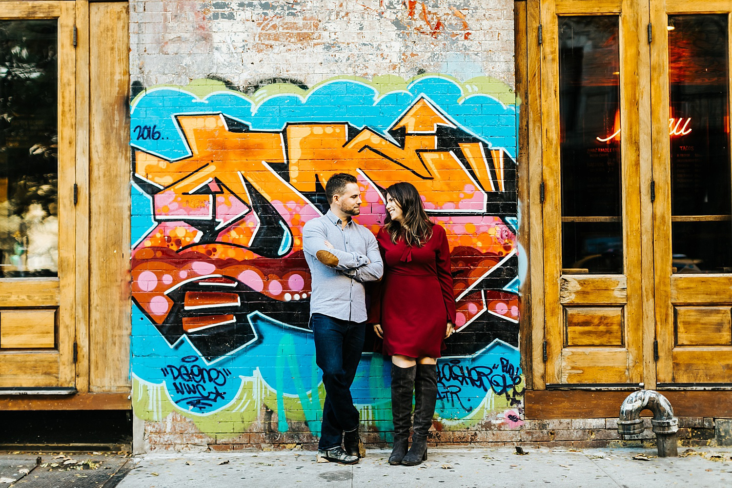 Engage couple standing in front of a graffiti wall in lower east side manhattan