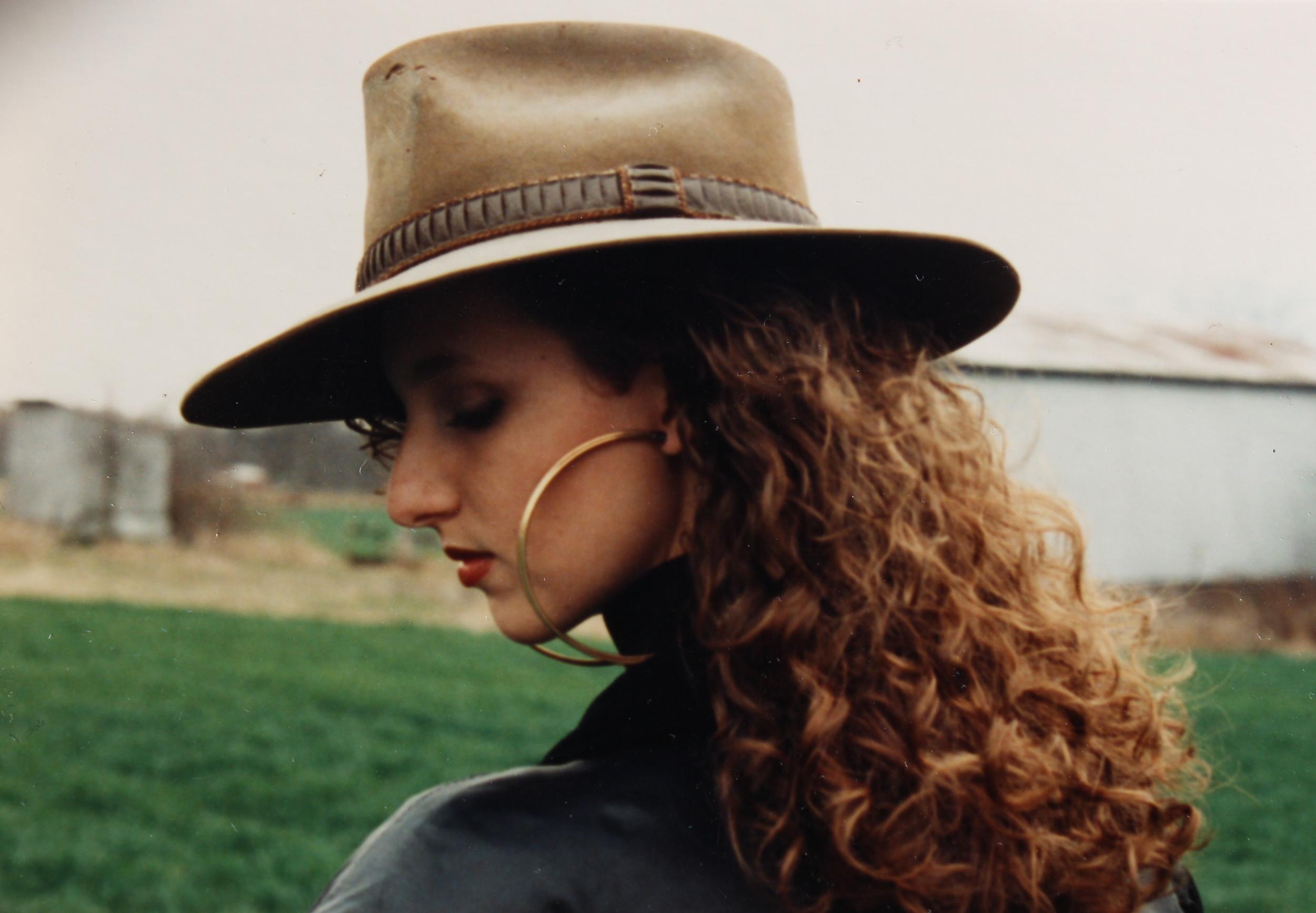 A hat wearing, big earring wearing college girl.