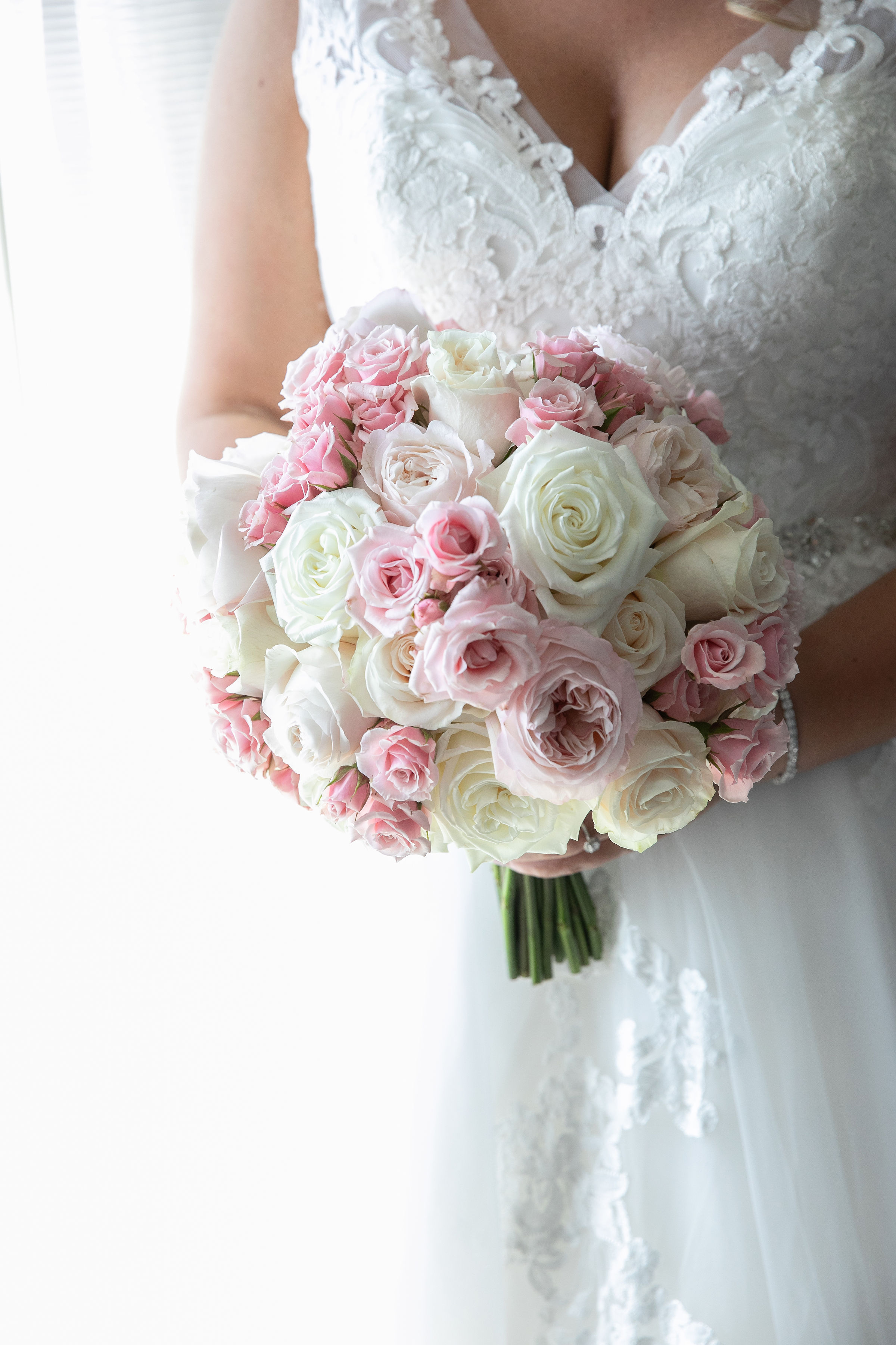Pink Spray Roses, Pale Pink Garden Roses, & Ivory Garden Roses are the stunning blossoms in this classically round bridal bouquet.   (Corinna Raznikov Photography)