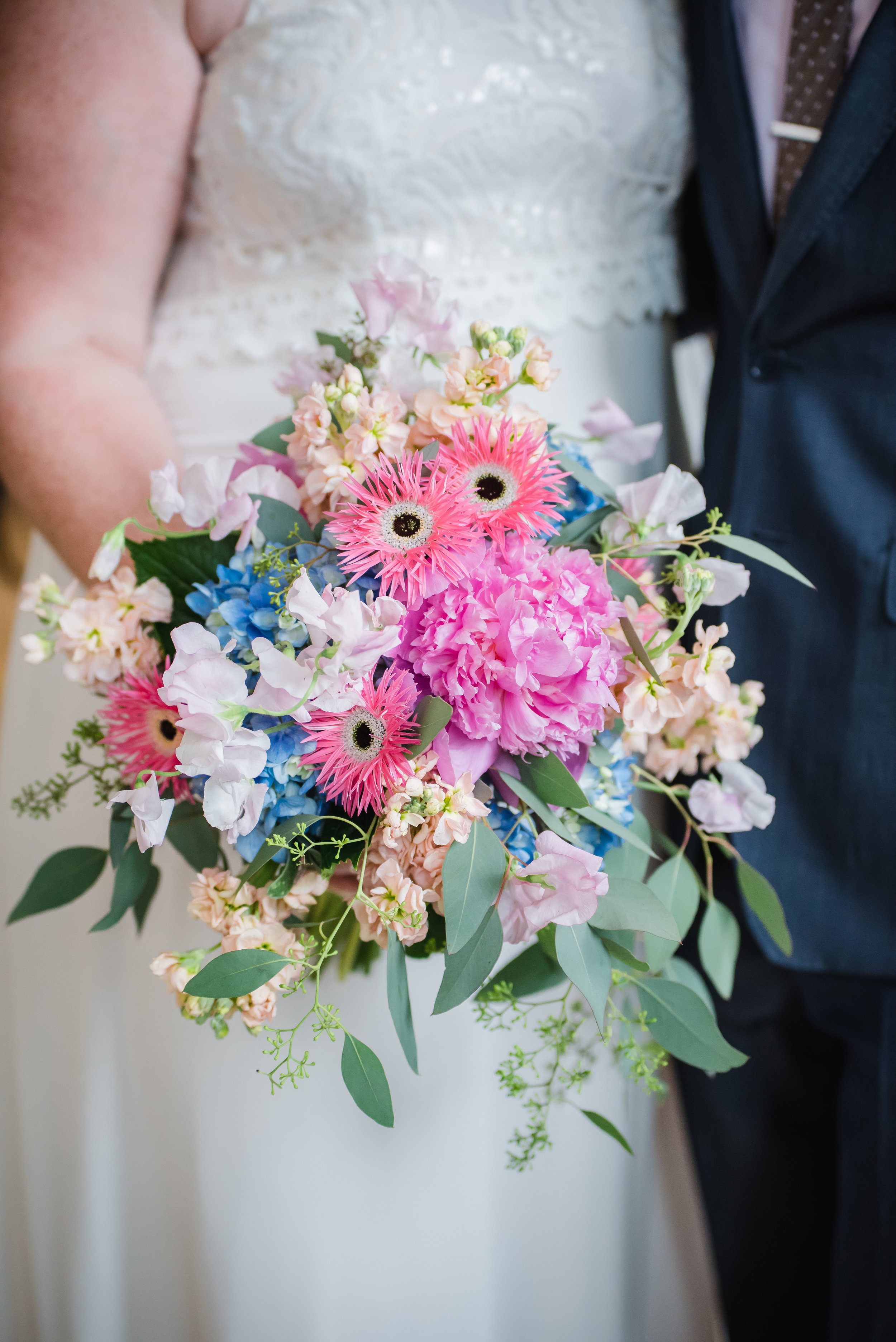 A fun and textural bridal bouquet with strong pinks and bright blues including Hot Pink Gerbera Daisies, Pale Pink Sweetpea, Peonies, & Hydrangea.  (Angelina Rose Photography)